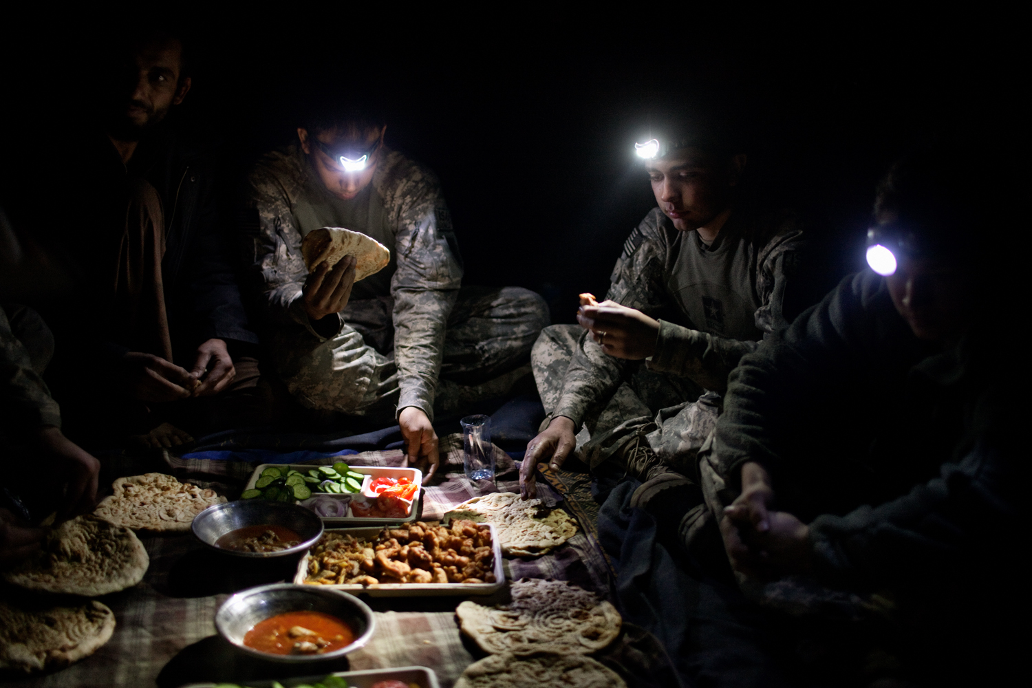 U.S. Army soldiers eat a meal prepared by Afghan labourers who work at Observation Post Dallas in the Korengal Valley, Kunar Province, Afghanistan.