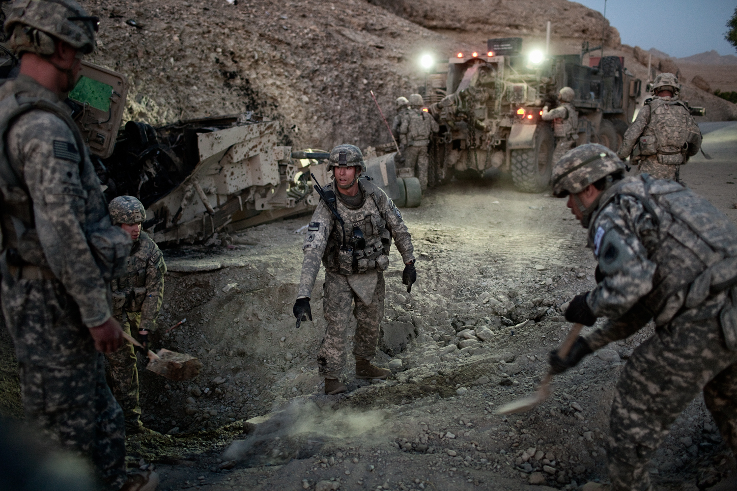 U.S. Army soldiers clear a road after animprovised explosive device attack on a vehicle in the Tangi Valley, Wardak Province, Afghanistan.