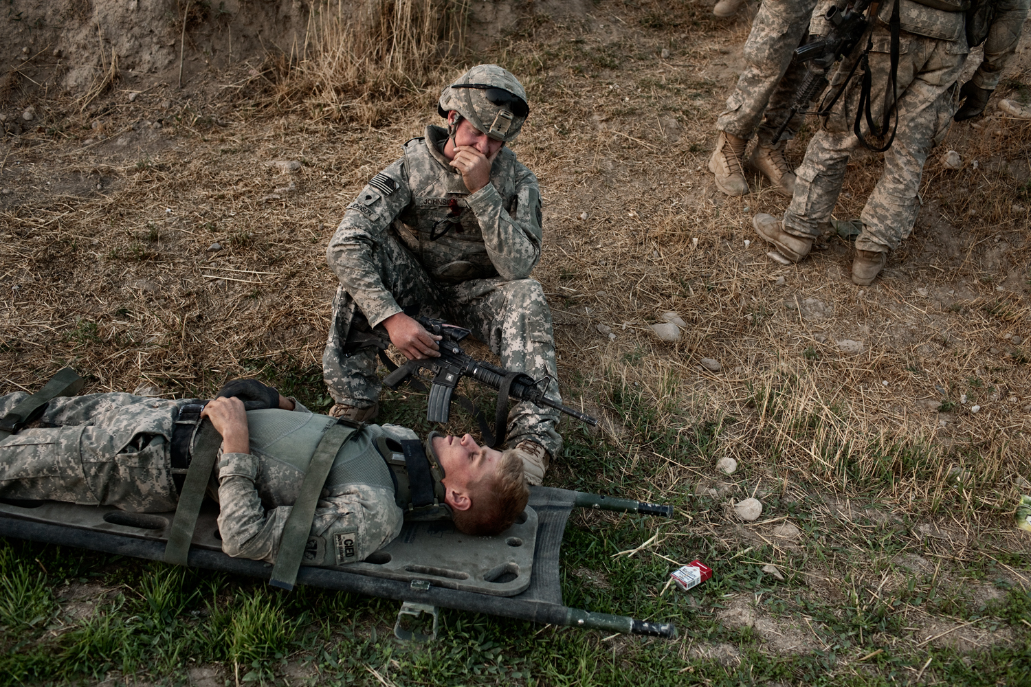 U.S. Army Specialist T.J. Fecteau lies on a stretcher after being concussed in an improvised explosive device attack on his vehicle in the Tangi Valley, Wardak Province, Afghanistan.