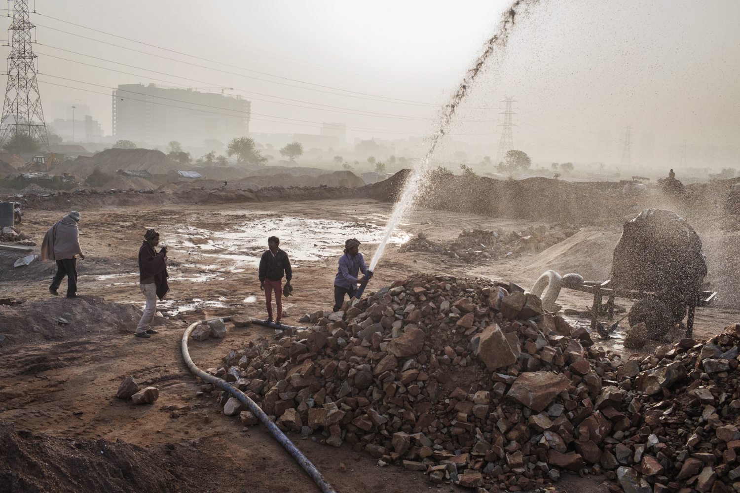 Indian workers wash stone before it is crushed into sand at an Illegal mine near Raipur Village in Greater Noida, Uttar Pradesh, India.