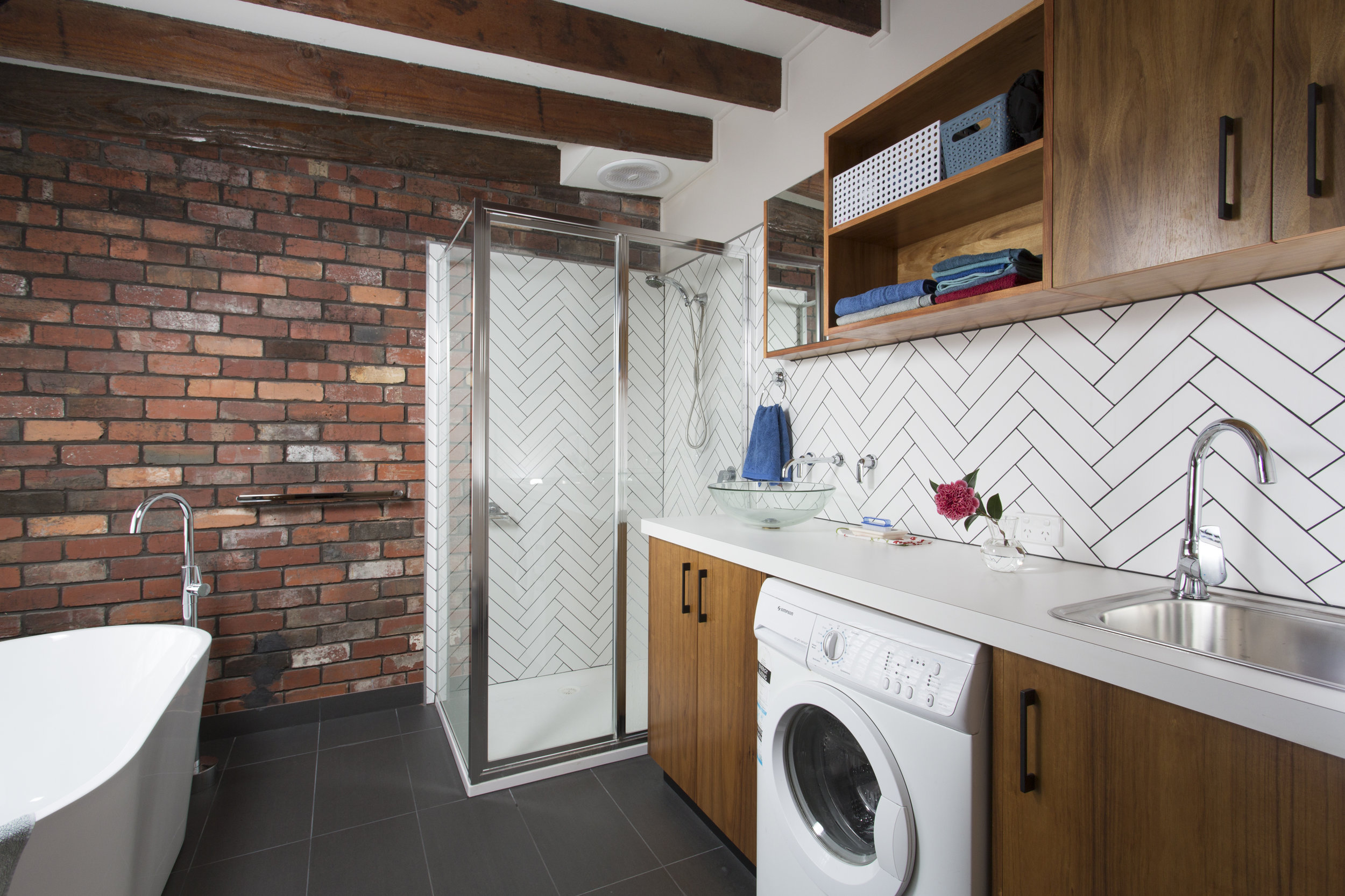 Laundry facilities built in to the large bathroom create a practical all in one wet area.