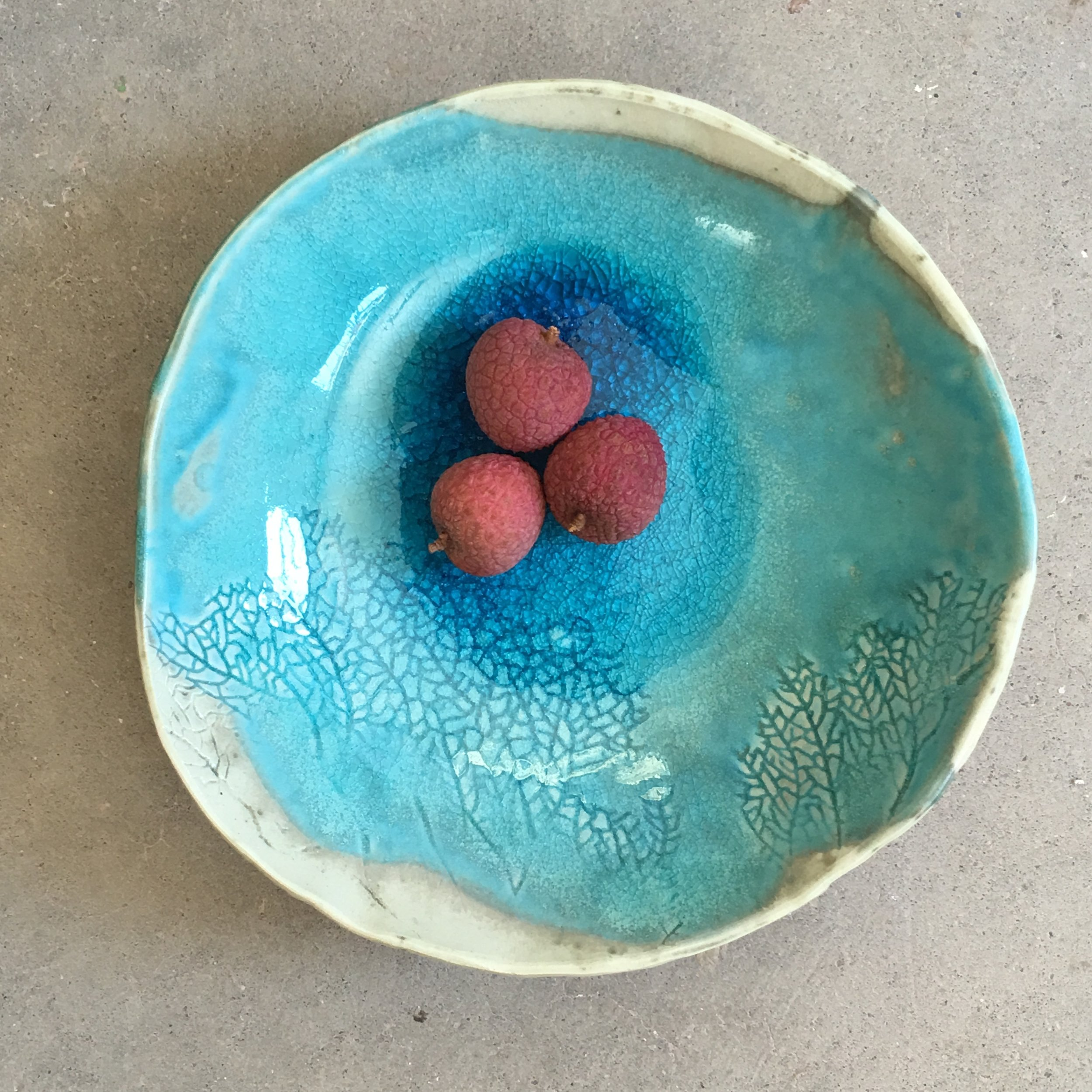 This is a white porcelain bowl with a gorgeous turquoise glaze and a coral print. It transports us to paradise islands and white sand beaches. I was such an honor to make lots of these to chef Suzi and ship them to the Middle East to Bahrain.