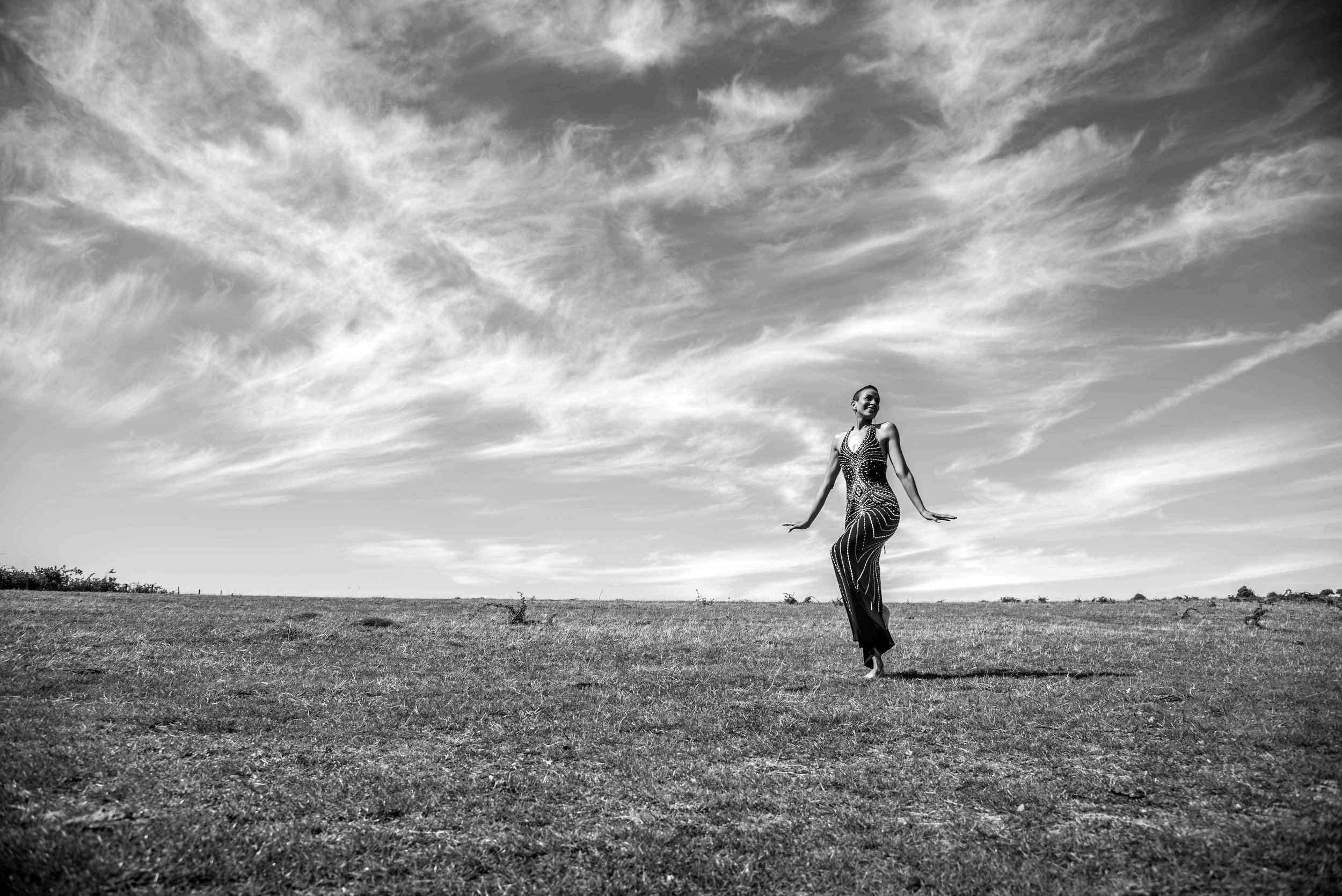 Beautiful woman in evening dress dancing on the downs.jpg