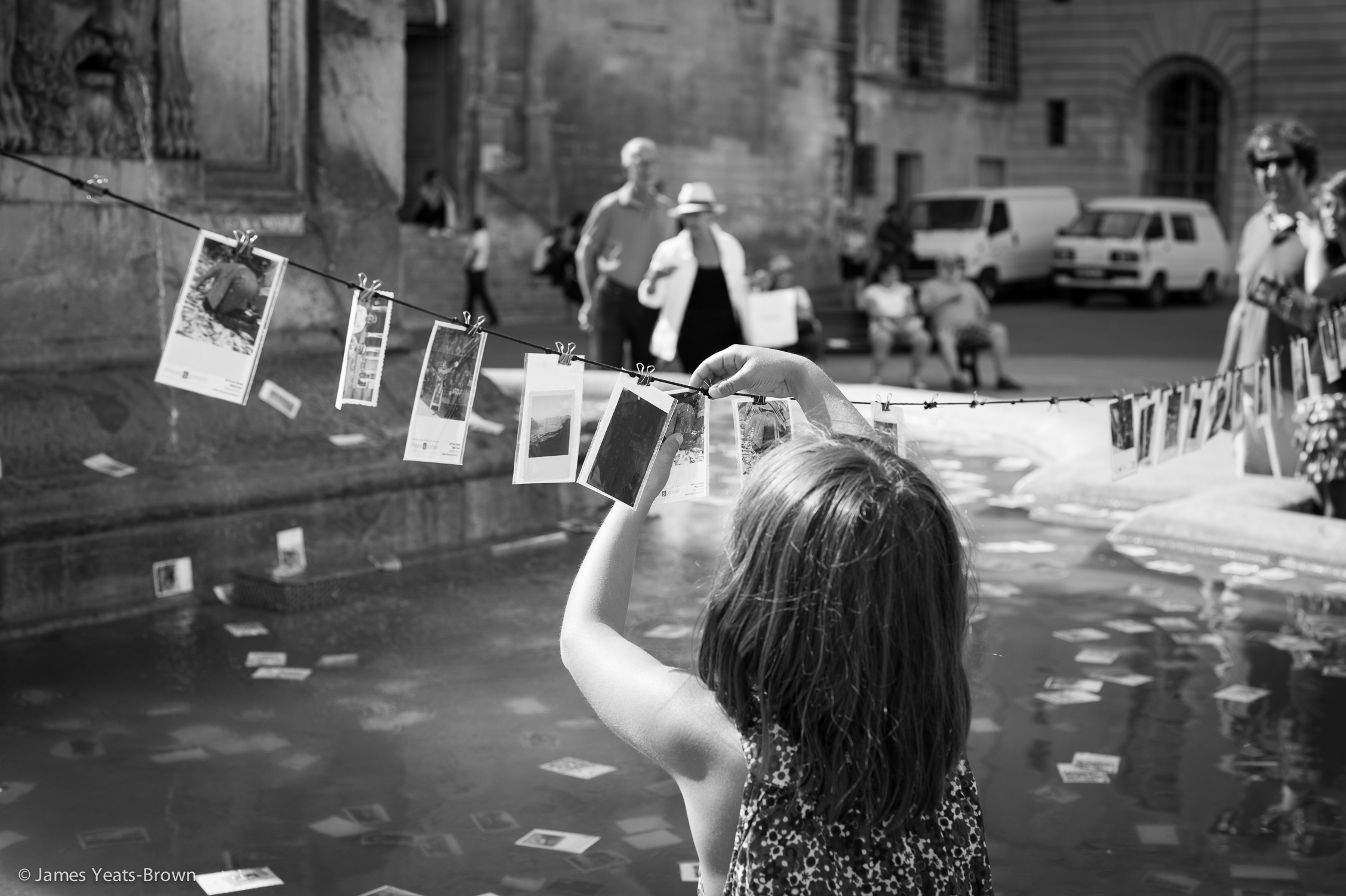 Putting images on line? A young girl picks out  photographies trouvées  from a fountain in Arles