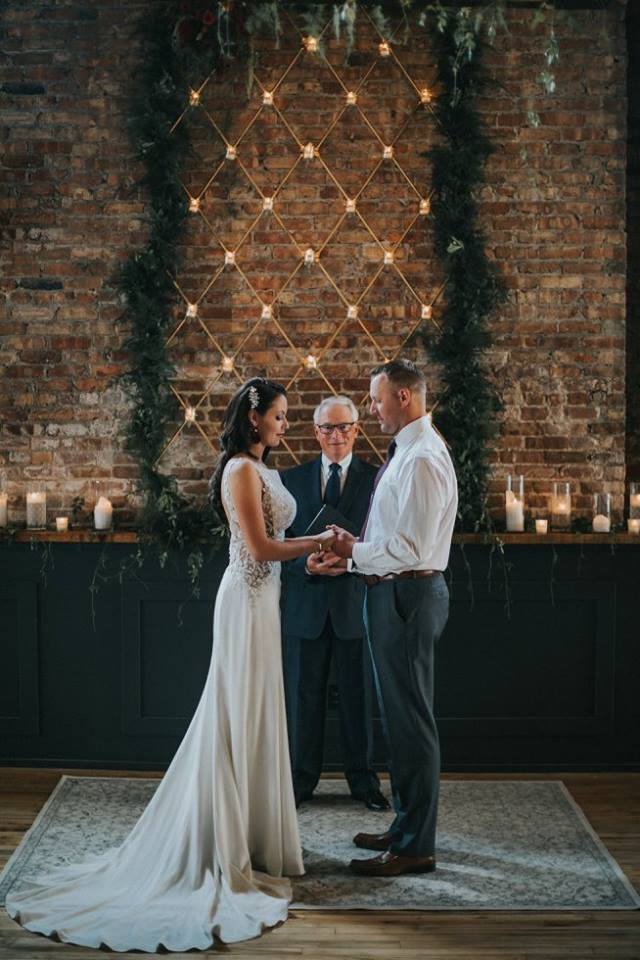 Couple getting married at Mercantile Hall. Bride is wearing a Maggie Sottero gown from Bon Bon Belle. Photo Credits: Floral: Jane Kelly Floral, Photography: Uttke Photography & Design, Hair & Makeup: Raw Salon & Spa  Bridal Accessories: Jaxie Bridal, Bridal floral earrings: Jane Kelly Floral
