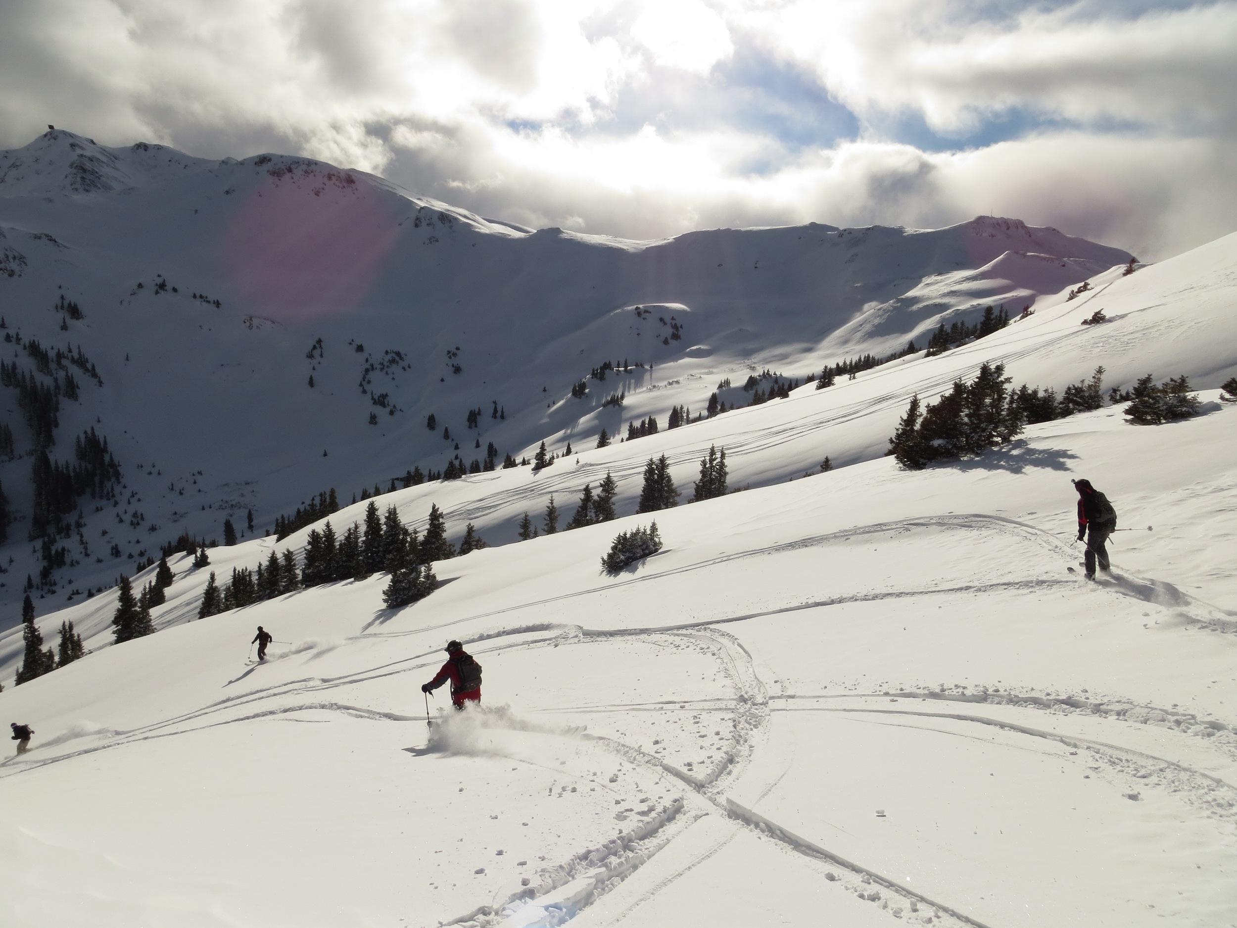Friends skiing fresh San Juan powder near Red Mountain Pass