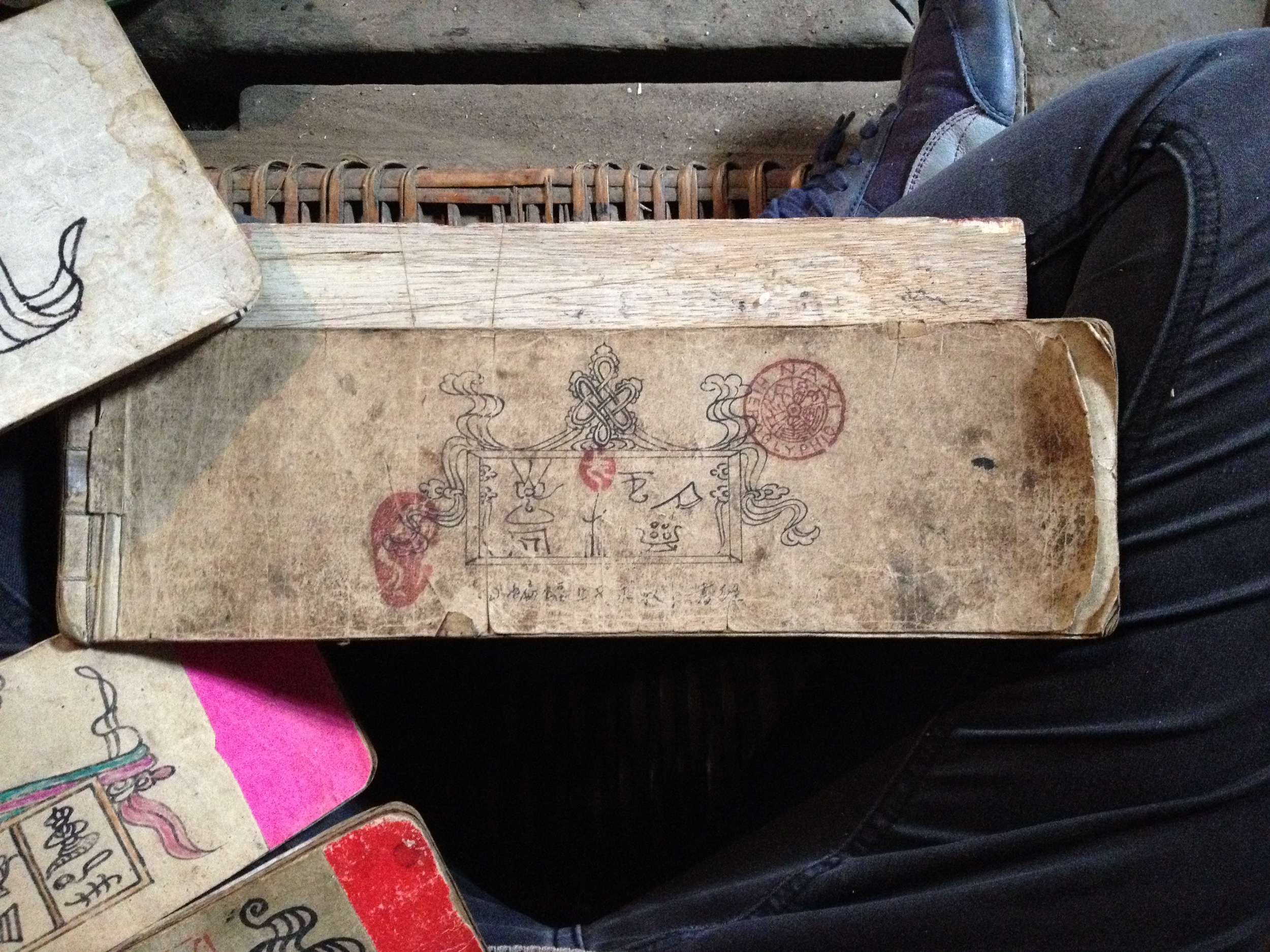 Thumbing through a selection of He Xiudong's Dongba scriptures in Tacheng. Featured above is a book drawn by his grandfather...