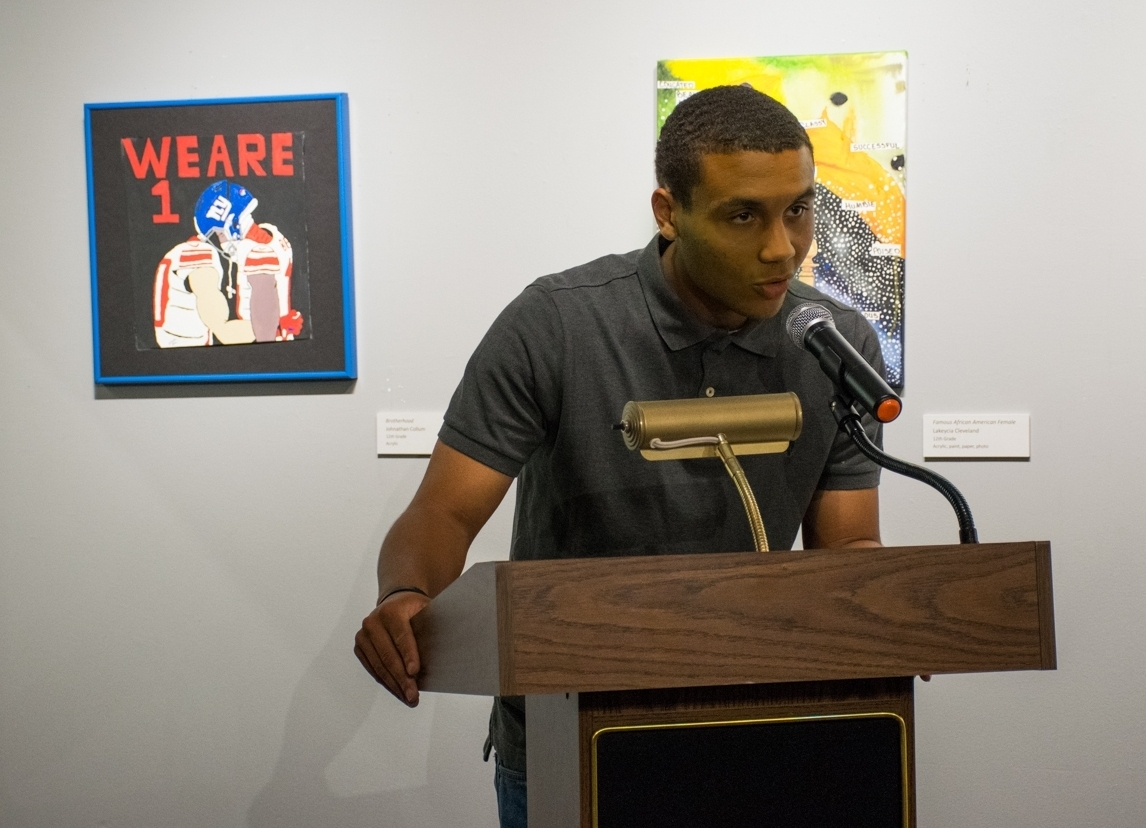 "Johnathon Callum, who recently graduated from PBHS, speaks during the May 3 opening reception. HIs piece, ""Brotherhood,"" seen to his left in the photo, ""depicts the image of two interracial players coming together during a political conflict,"" Johnathon explained in his artist statement."