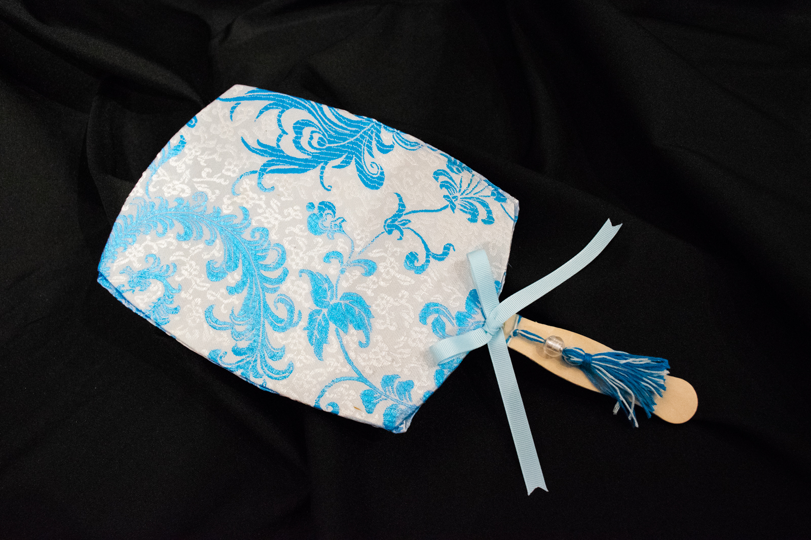 """""""Sumptuous Silks and Ancient Traditions"""" Attendees will be guided in making their own personalized fans like the one shown. Inspired by a variety of traditional Chinese hand fan designs, the silk brocade fans can be personalized to the makers' taste. They can also enjoy a complimentary wine or beer while making their fans."""