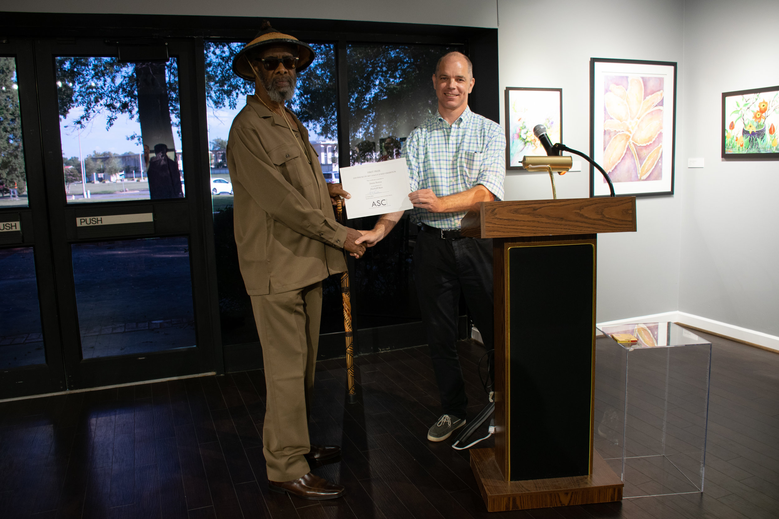 """Jimmie L. Burton won First Place for his acrylic painting """"Fourth & Main."""" Juror John Kushmaul announced the winners."""