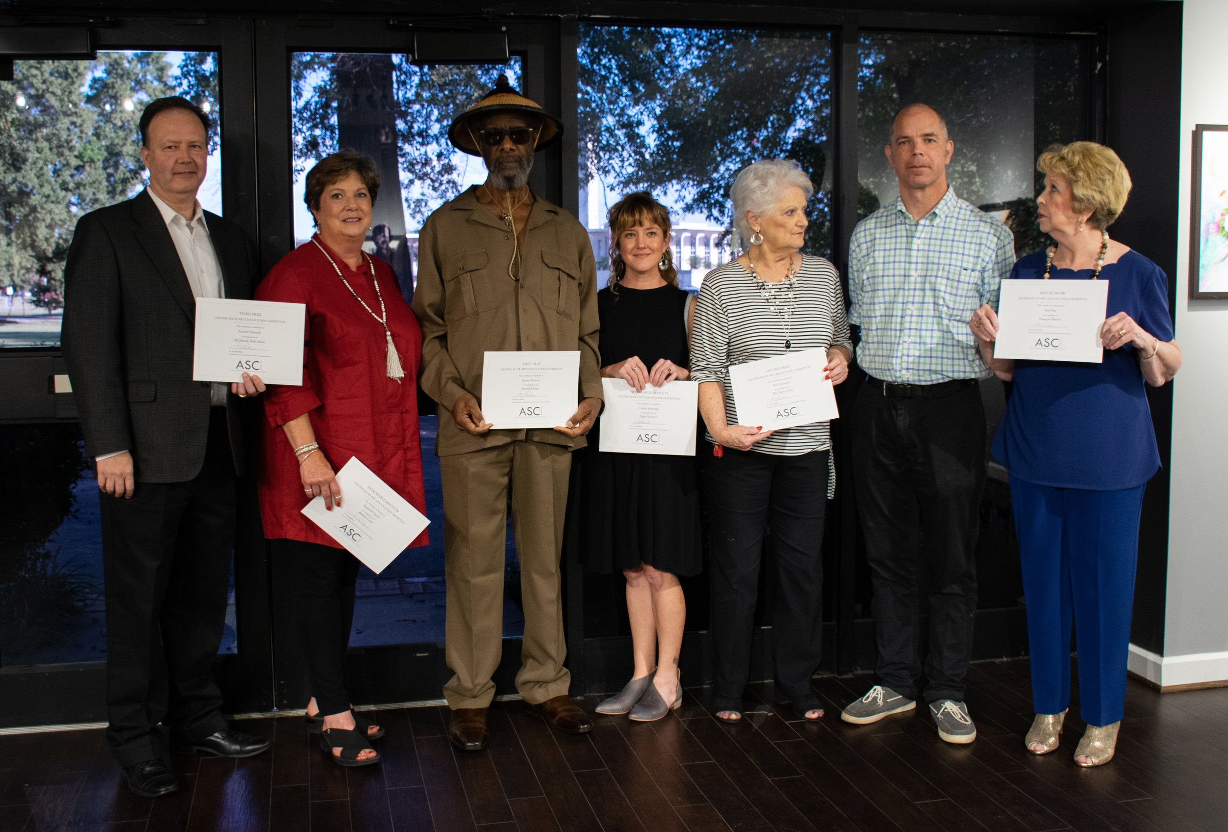The winners of the 2018 Pine Bluff Art League Annual Exhibition are (from left) Patrick Edwards (Third Place), Elizabeth Sadler (Honorable Mention), Jimmie L. Burton (First Place), Crystal Jennings (Honorable Mention), Dell Gorman (Second Place), Juror John Kushmaul, and Inis Ray (Best in Show).