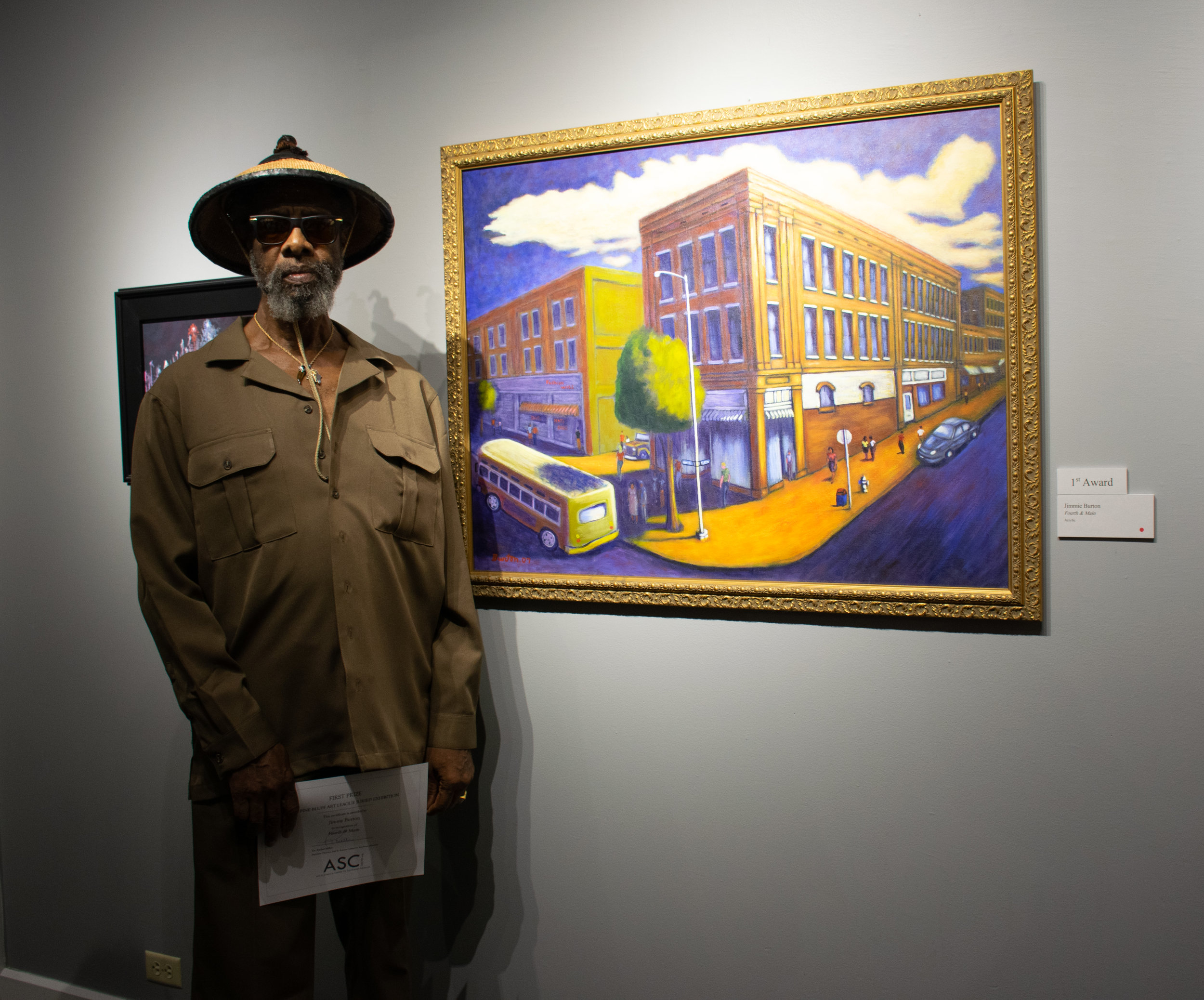 """Jimmie L. Burton with his painting """"Fourth & Main,"""" which won First Place."""