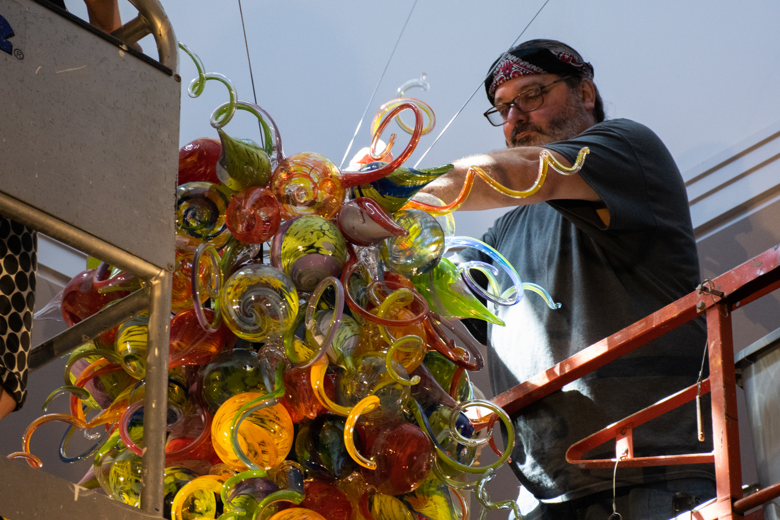 "Artist James Hayes installs his blown glass sculpture, titled ""Celebration Chandelier,"" on Sept. 20, in the atrium of the Arts & Science Center for Southeast Arkansas in Pine Bluff. A public reception for the unveiling of sculptures by Hayes and fellow Pine Bluff-born artist Kevin Cole is scheduled for 5 p.m. Thursday, Oct. 18, at the Arts & Science Center."