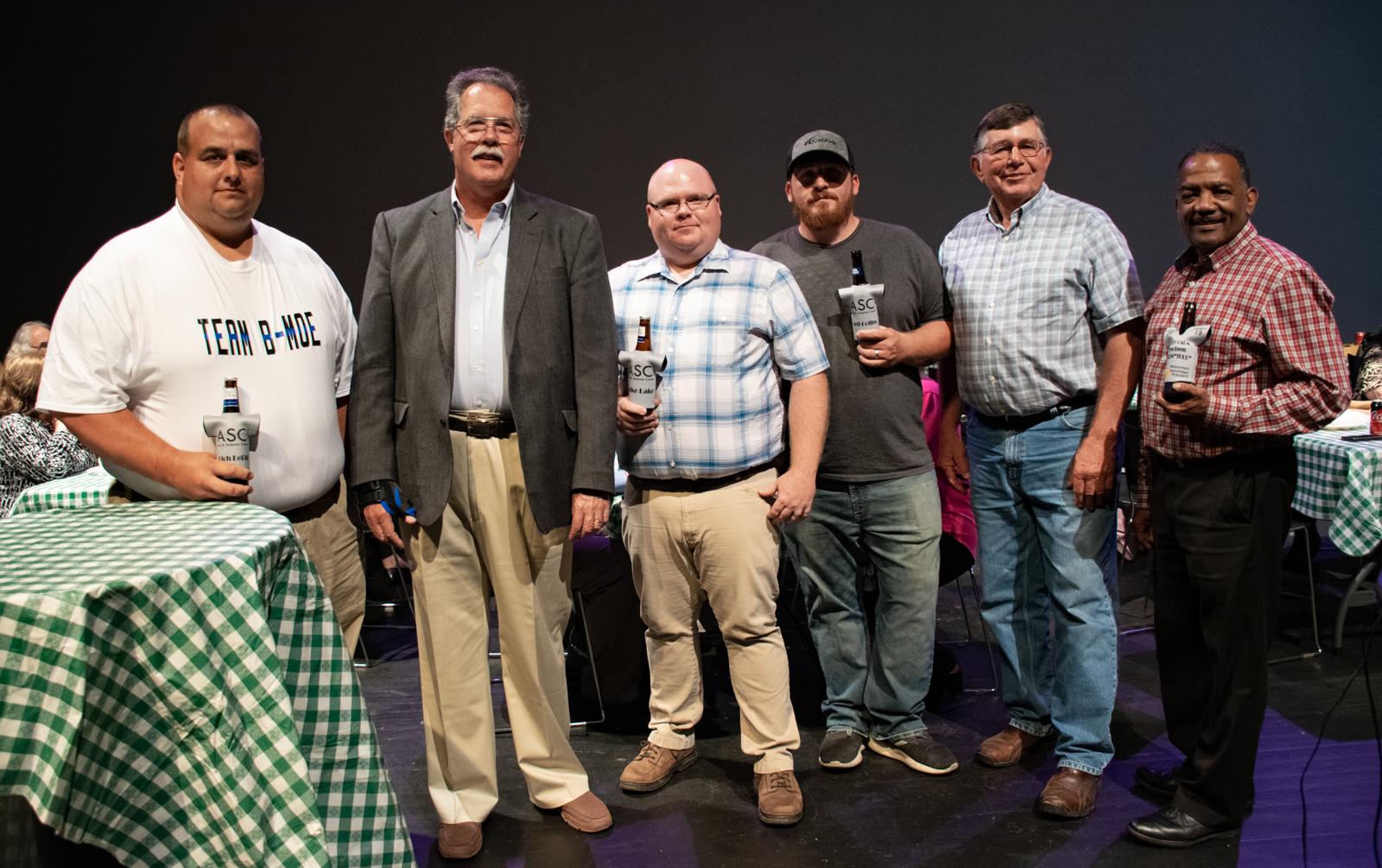 "Rich DeBill (from left), Michael Healy, Mike Lake, Jeff Collins, Mike Kline, Kenny Fisher and Scottie Abernathy (not pictured) were honored ""for their continued patience and willingness to be volunteered by their significant others for countless ASC events, productions, and programming"" with awards dubbed ""The Volun-Tolds."" The honorees received personalized beer ""huggies"" from NovelTs."