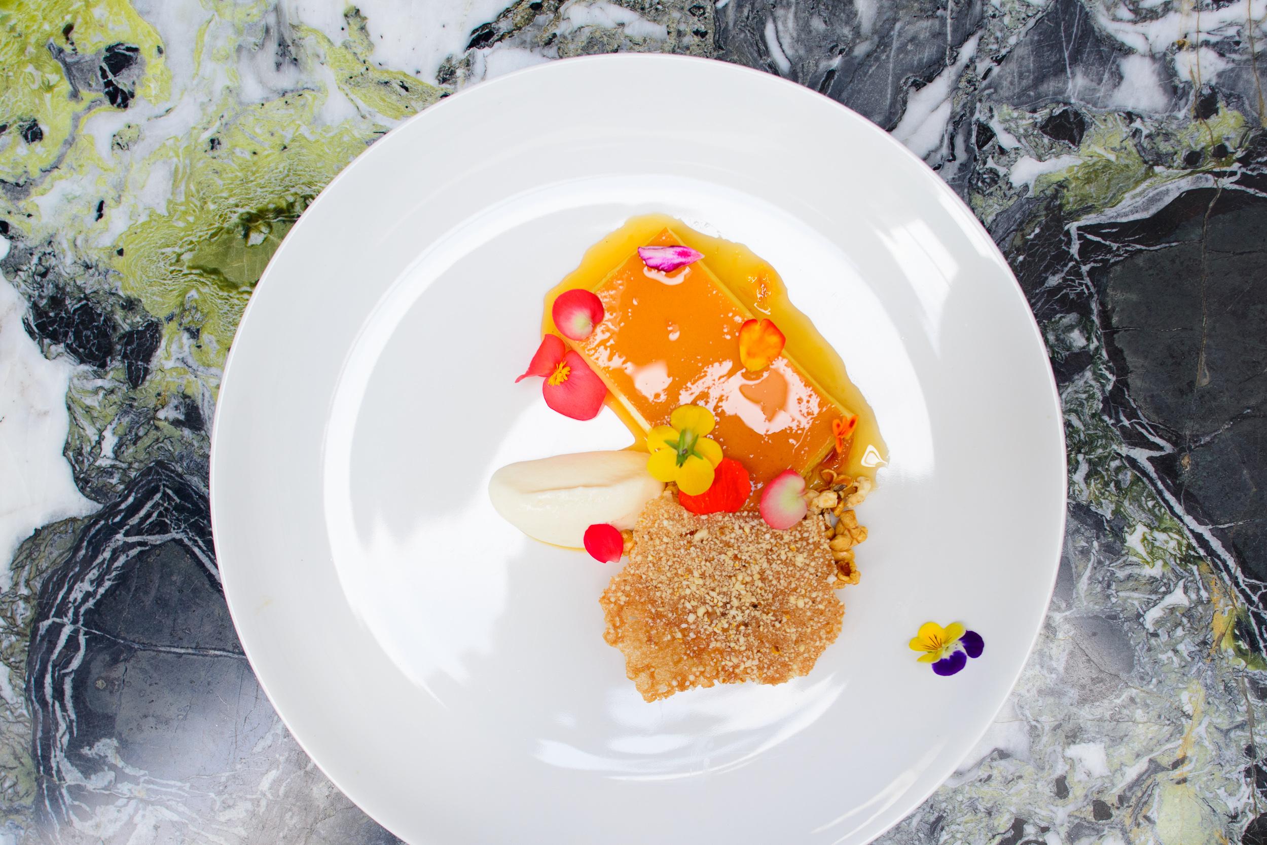 Flan casero con salsa de naranja: flores comestibles y palomitas