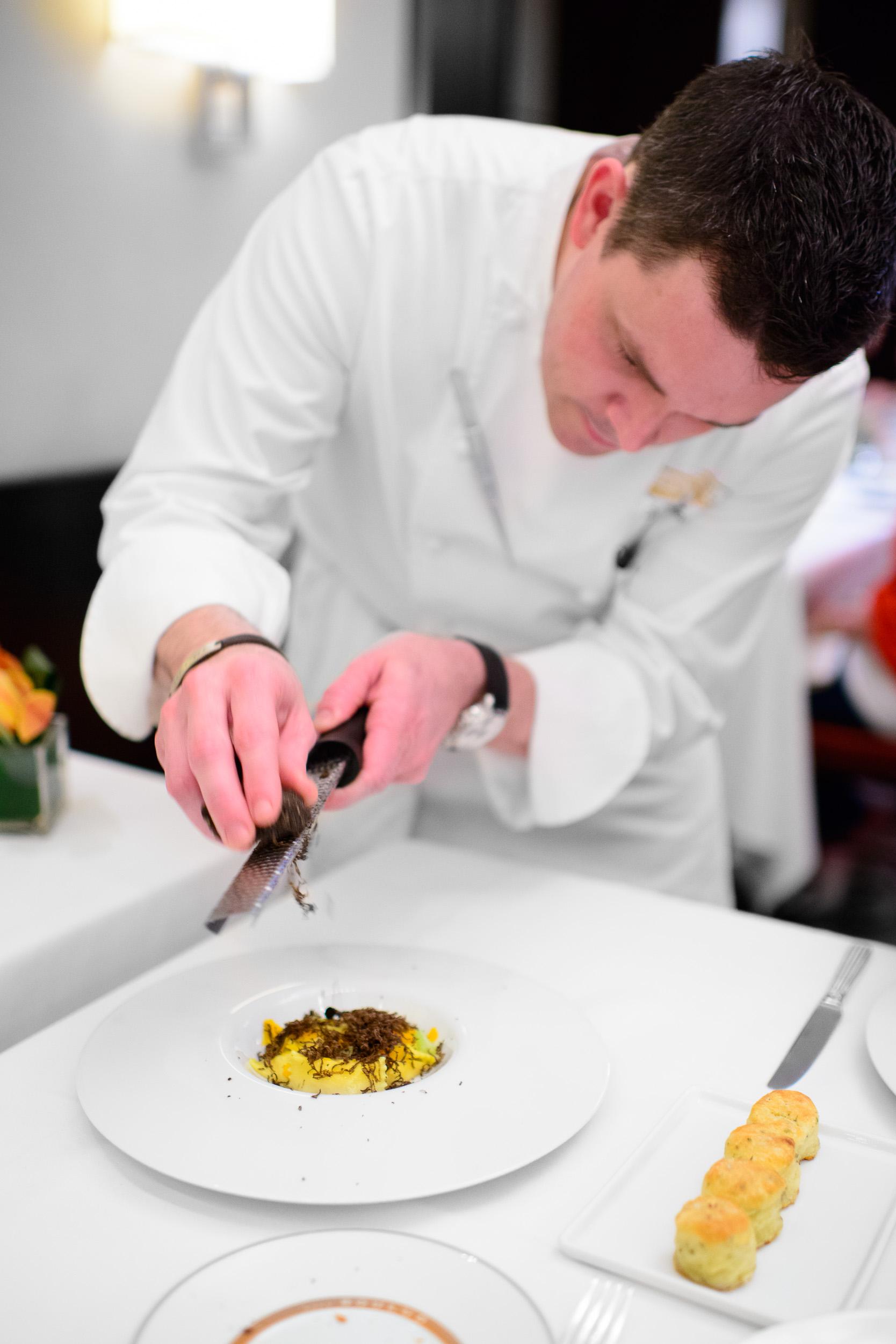 Chef Gavin Kaysen shaving black truffle over the celery root agn