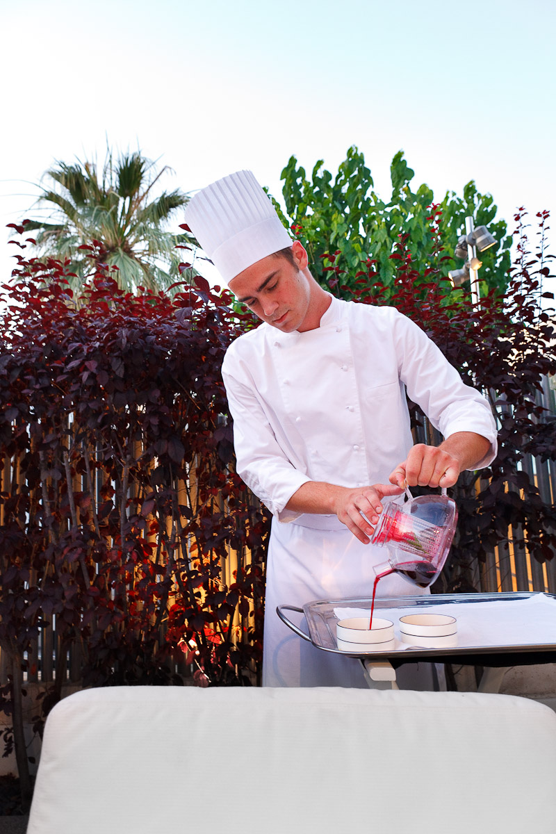 Chef pours cold tea of chicory and hibiscus