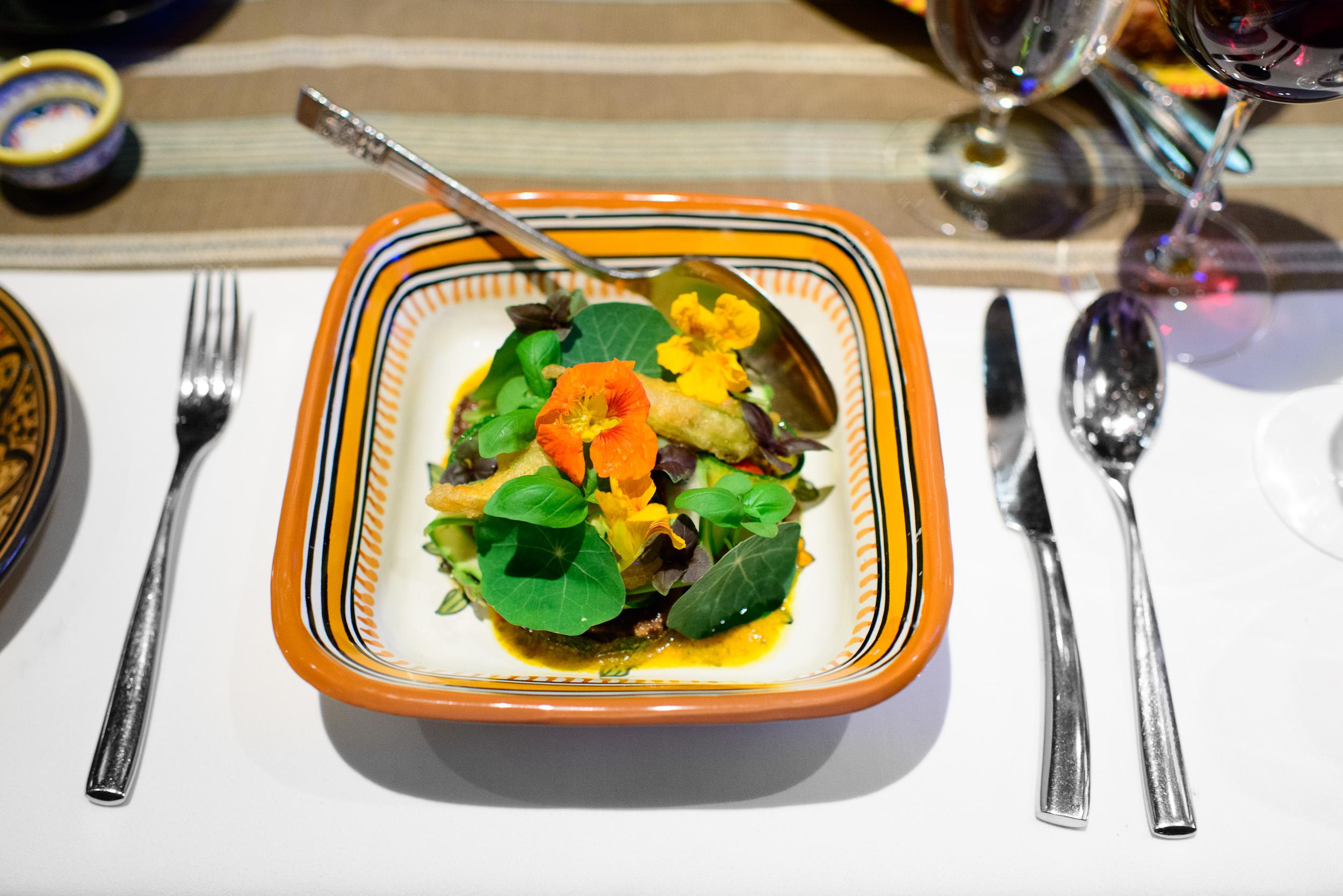 6th Course: Slices of zucchini and squash blossoms in a tomato v
