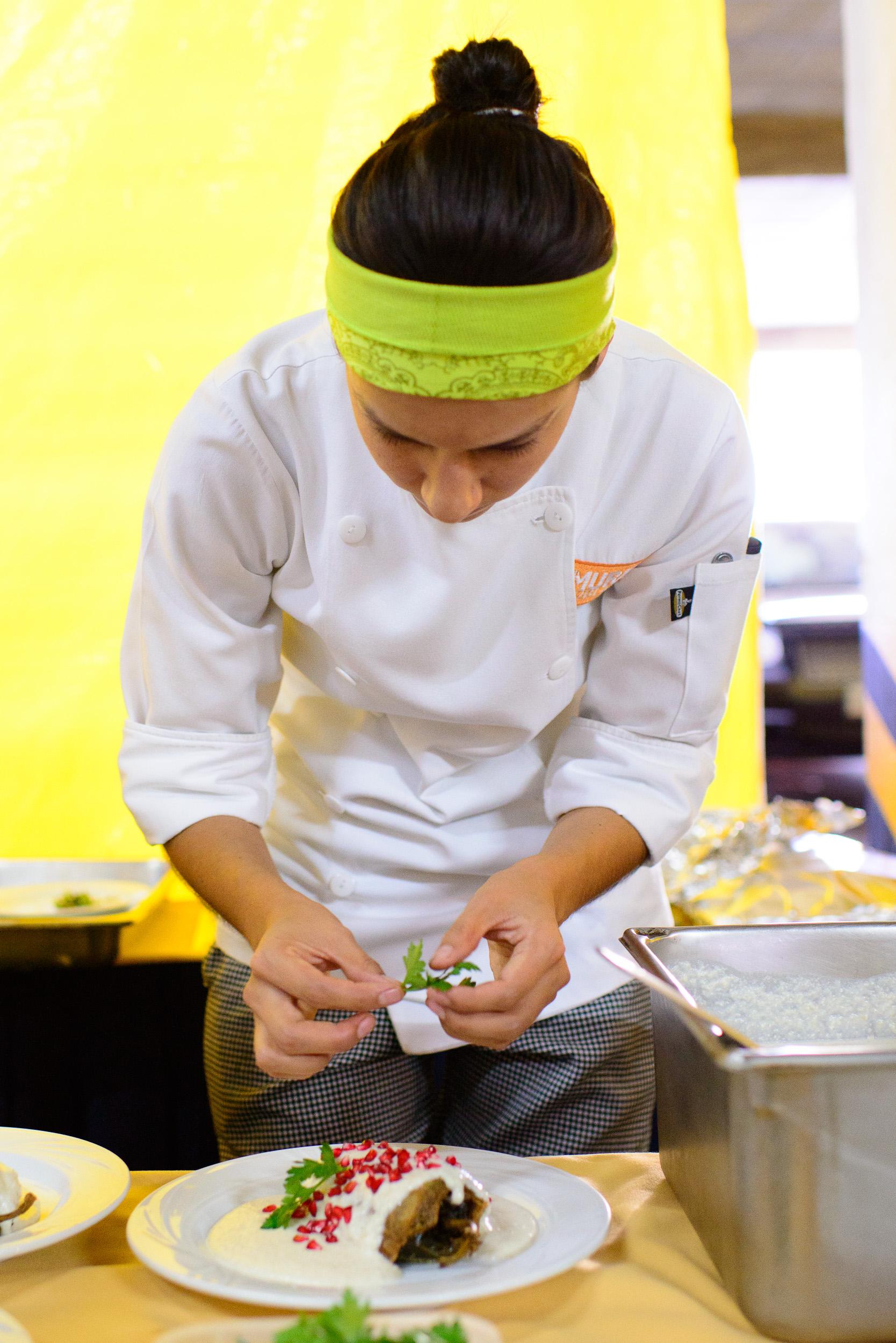 Chef Liz Galicia of El Mural de los Poblanos plating chiles en n