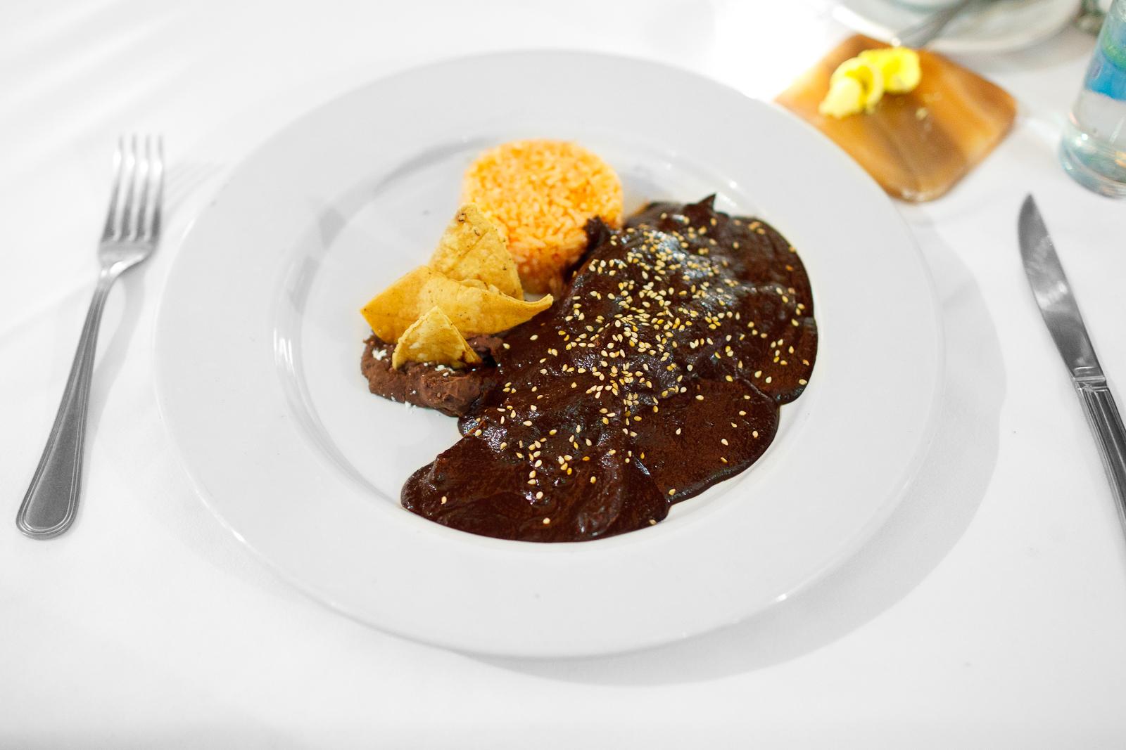 Mole Poblano de pato, hecho a base de chiles secos, frutos, chocolate, semillas, y especias (Pueblan mole over duck) ($195 MXP)