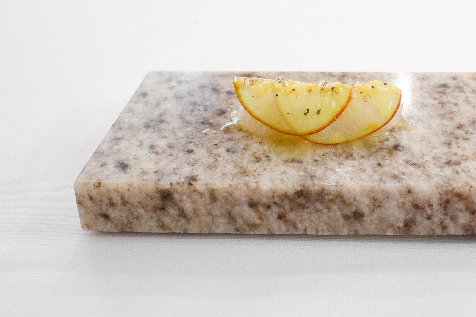 Amuse Bouche: Roughly chopped raw langoustine from Ingemar Johansson under autumn apple shavings, rosemary, and almonds.