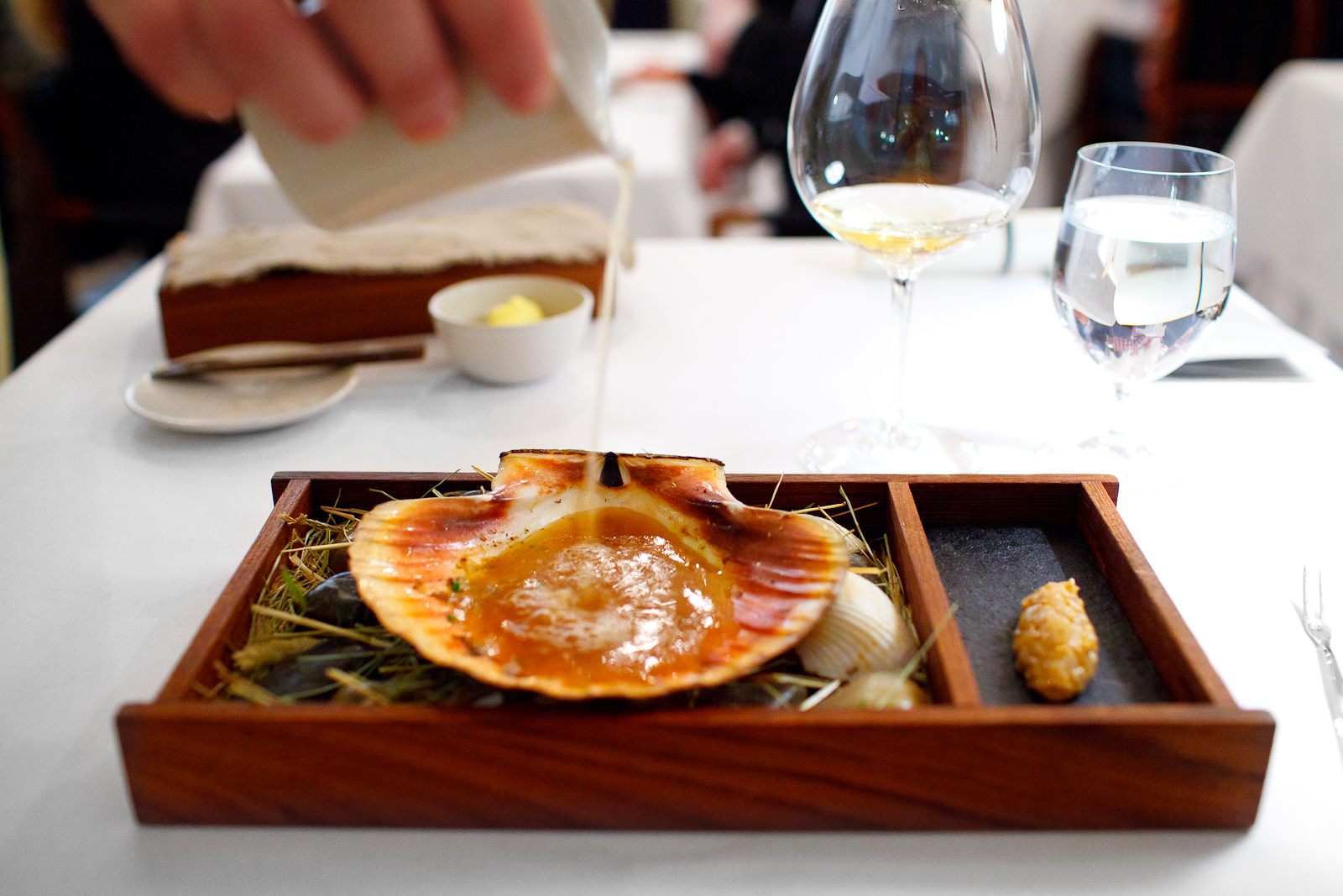 3rd Course: Scallop from Trondheim, Norway in two servings. Second, raw marinated and bound in confit of the roe with a bouillon of dried scallops, algae, and dried girolles.