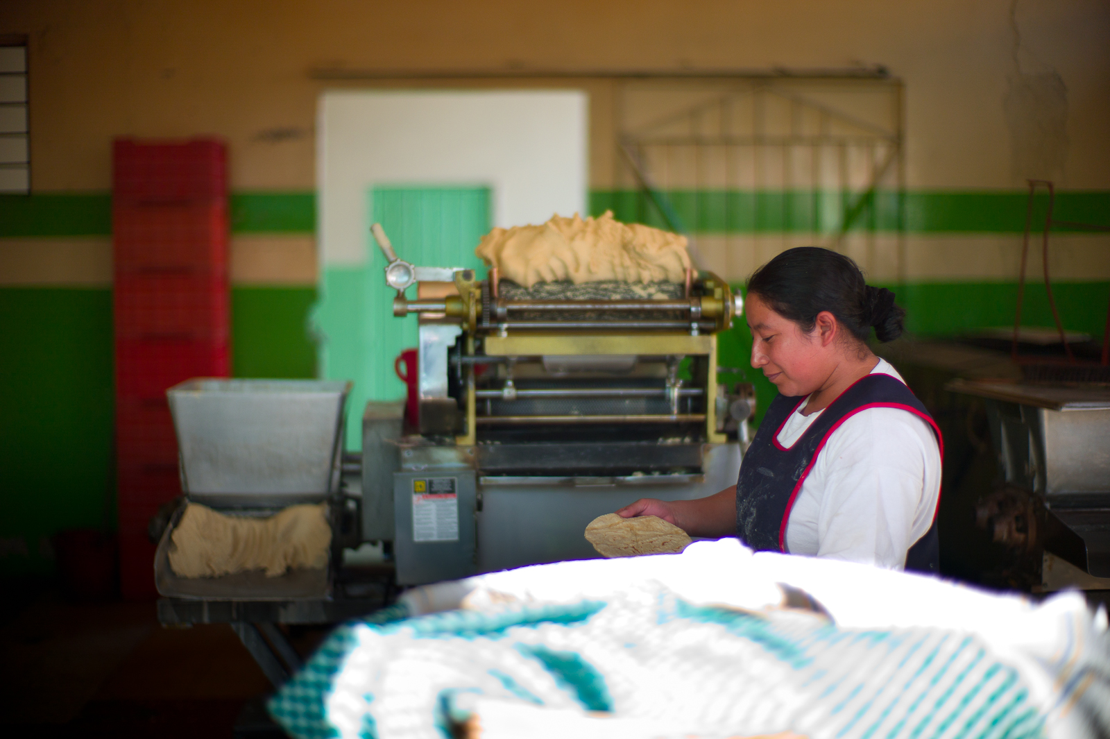 Tortilla maker working the masa