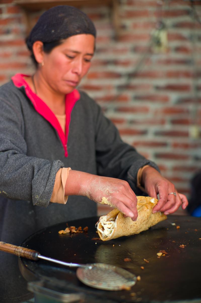 Flipping a quesadilla de chicharrón, quesillo, y epazote (15 MXP)