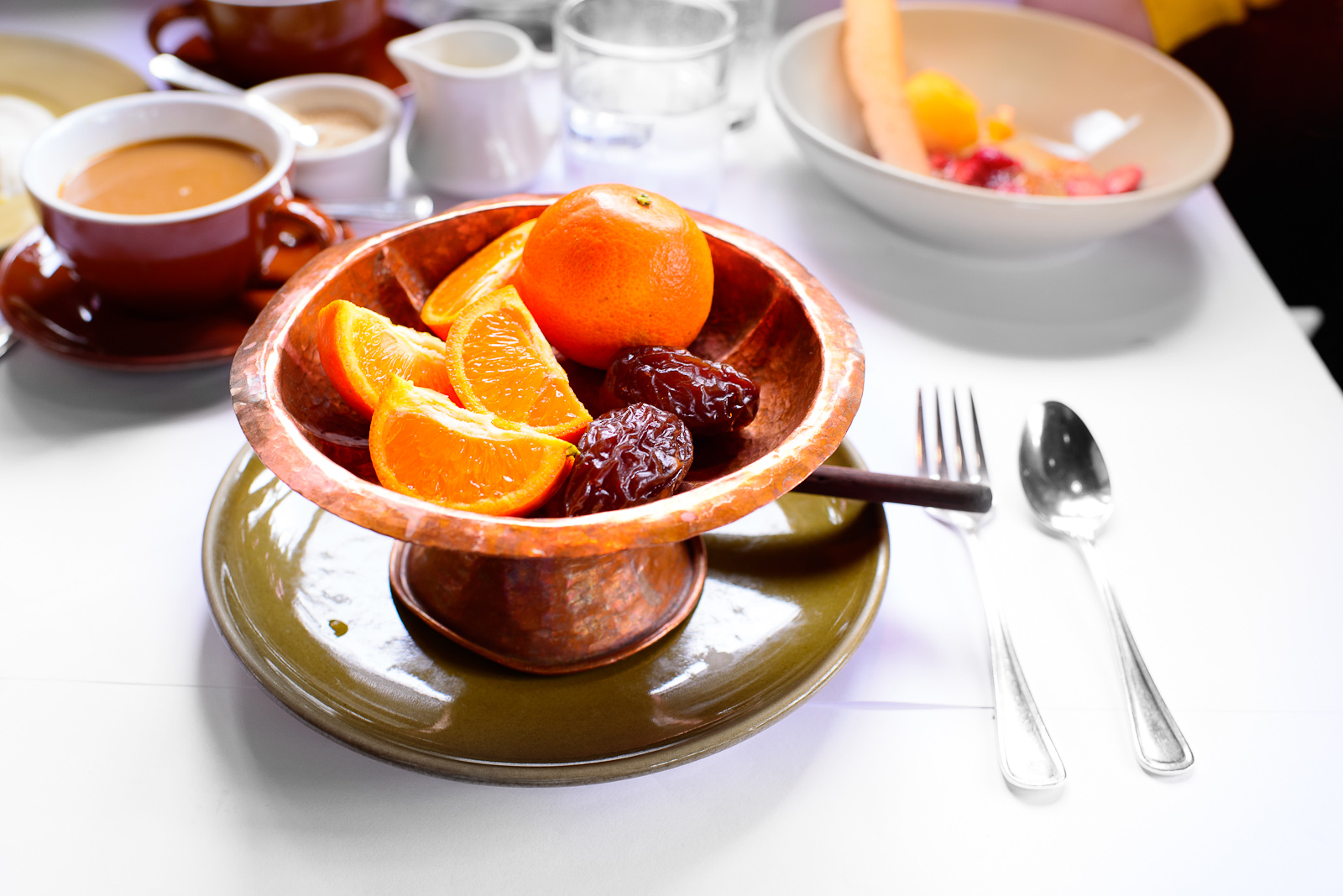 A bowl of Churchill-brenneis Orchards Page mandarins and Medjool