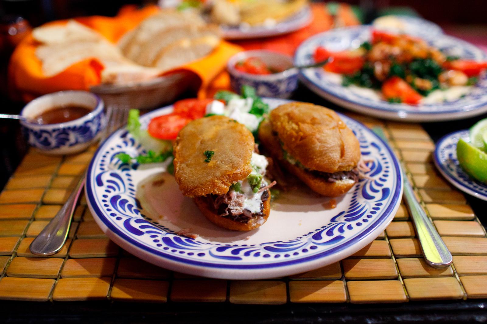 Guajolotes - pan especial de ague, frito y relleno de frijoles, guacamole, creme, salsa verde, y carne de res deshebrada