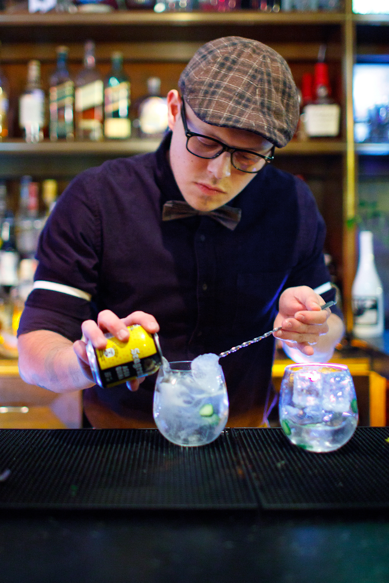 Making a Gin & Tonic. Pouring tonic water over a spoon to balance the carbonation.