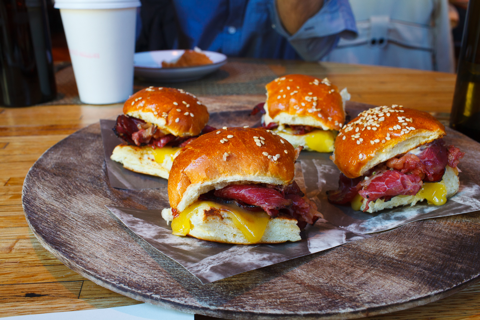 Slices of 45-day dry aged 3-day cured beef with a garlic and black pepper crust smoked for 16-hours on a benne buttermilk bun, cheese, tomato aïoli, garlic