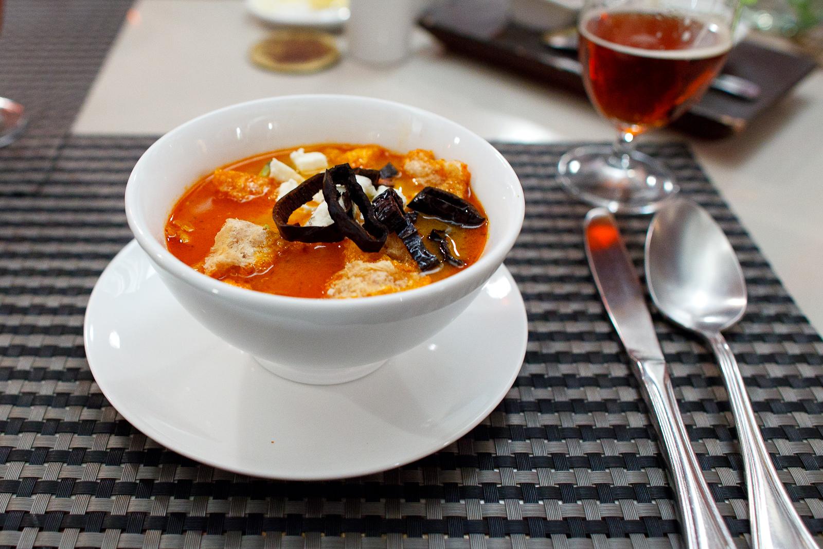 La sopa Azteca, tiras de tortilla en caldillo de jitomate servido con trocitos de aguacate, chile pasillo, chicharrón, queso fresco y crema de rancho (60 MXP)