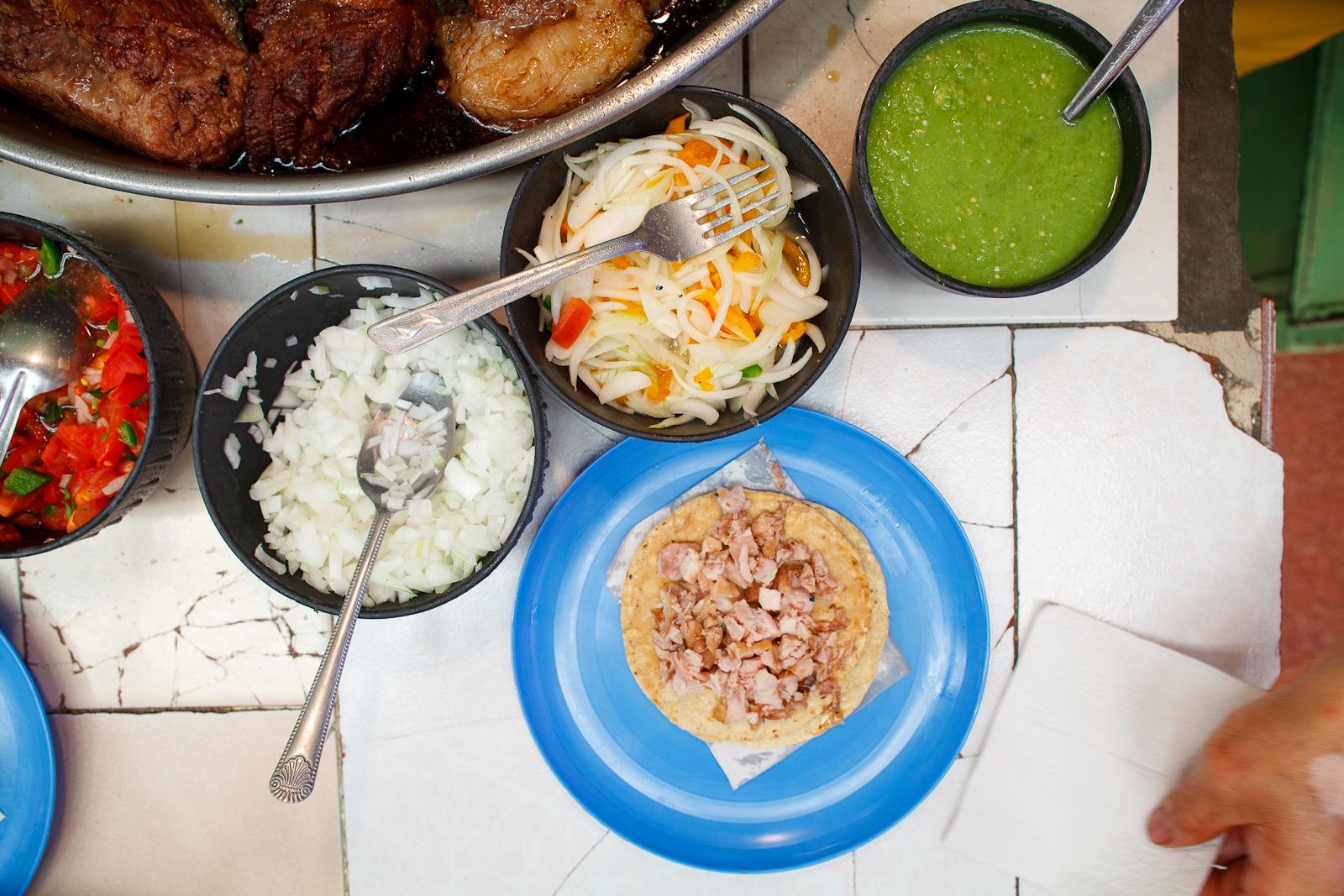 Taco de carnitas (pork) with salsa verde, habanero, onion, and pico de gallo
