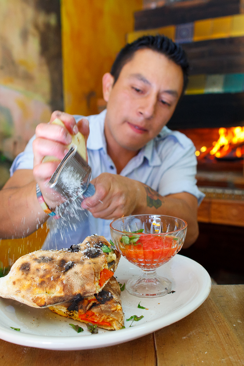 Sprinkling parmesan on a calzone margherita with mozzarella and salumi (70 MXP)