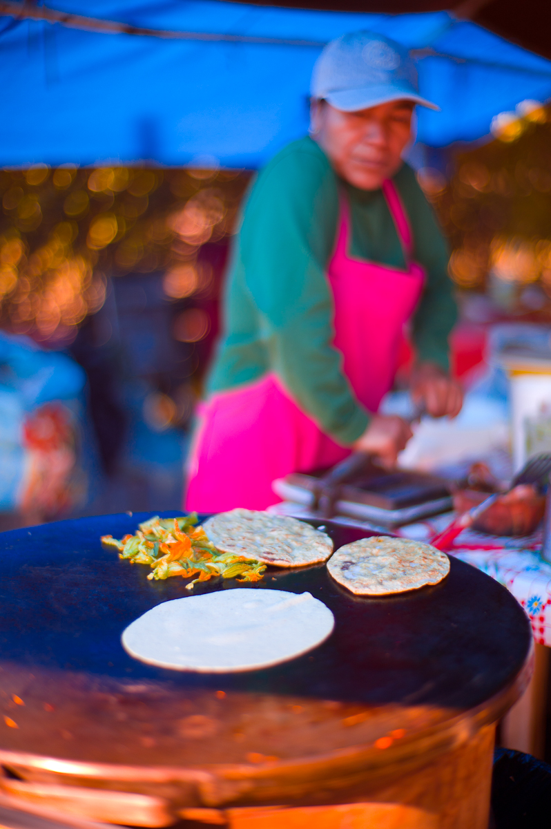 Pressing a tortilla for a queca de huitlacoche