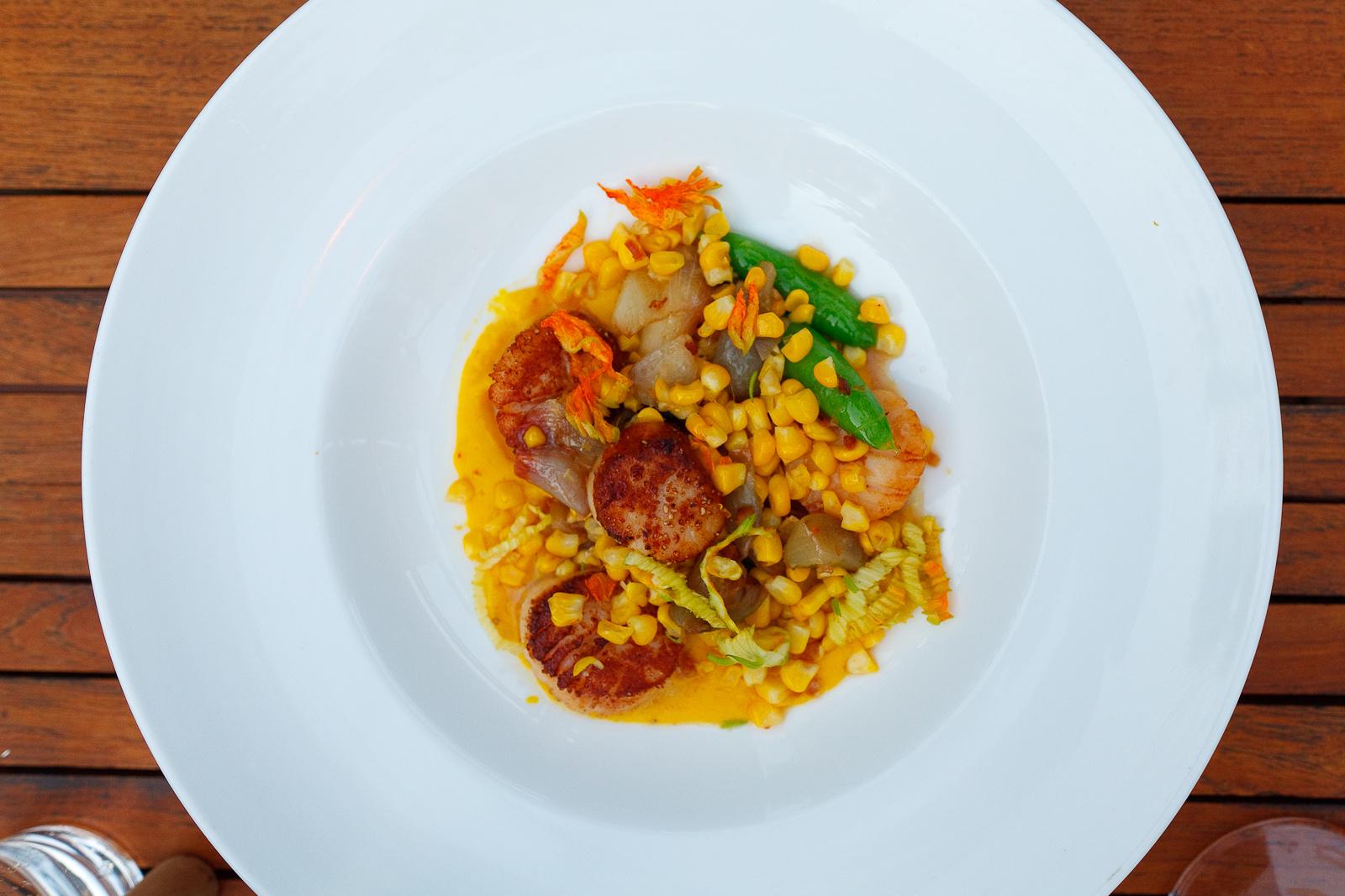 Pan seared scallops, saffron-corn puree, snap peas, corn shallots, squash blossom, bacon vinaigrette ($26)