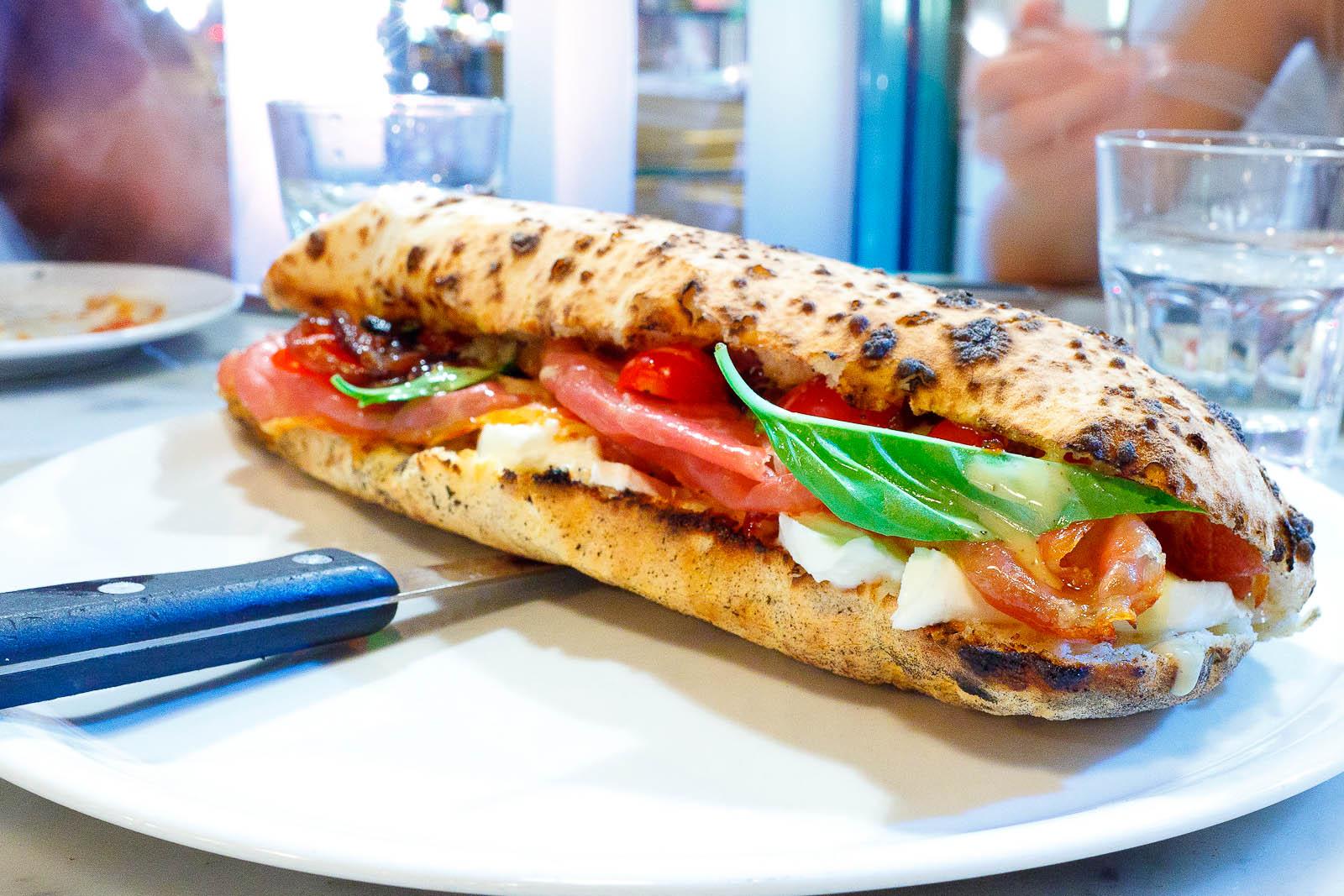 """Calzone hero"""" - Prosciutto di Parma, mozzarella di bufala, caramelized onions, mustard, cherry tomatoes, basil"""