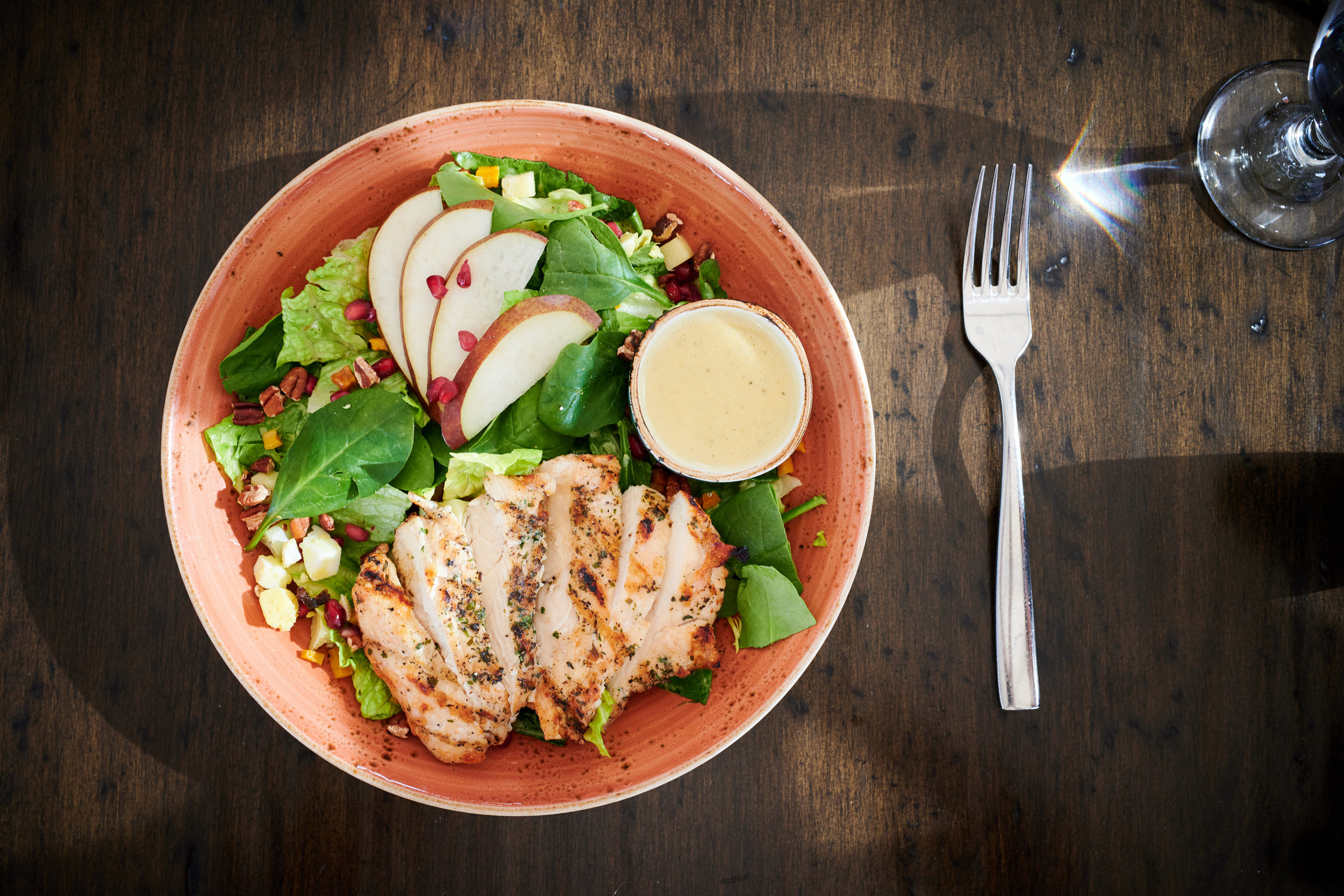 Harvest Cobb Salad with Grilled Chicken, Romaine, Mixed Greens, Grilled Pears, Bacon, Egg, Smoked Cheddar, Pomegranate, Butternut Squash, Pecans, Apple Cider Vinaigrette