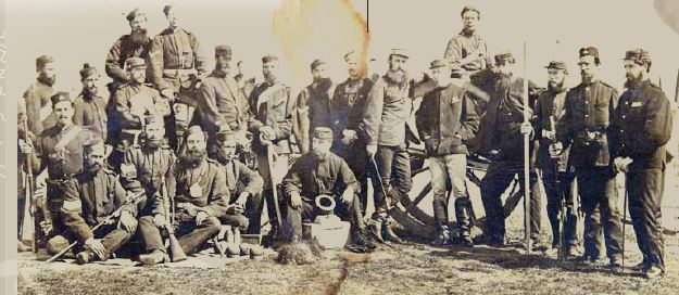 """Awaiting the order to advance"" (for the battle of Gate Pa). Taken at sunrise on 29 April 1864. General Duncan Cameron is leaning on the wheel of the gun carriage, (fifth from right)."