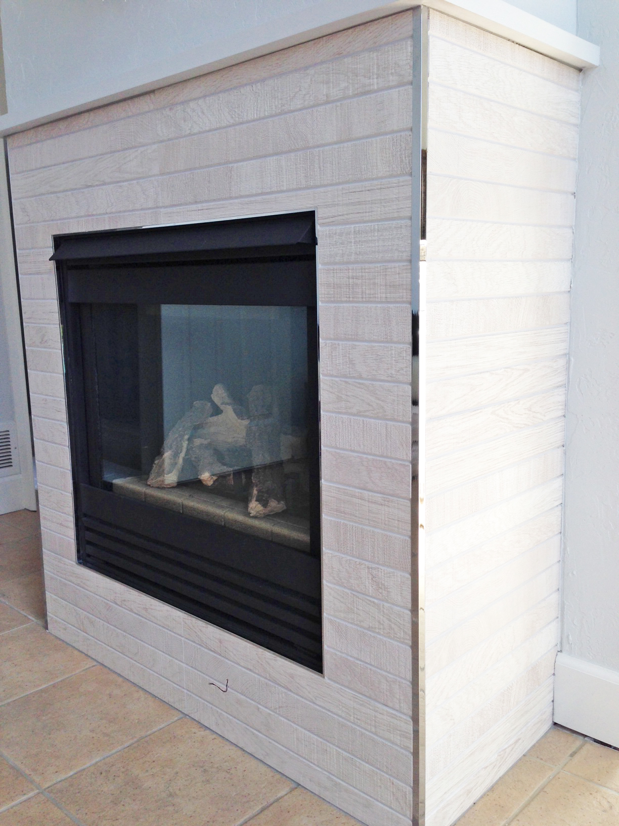 I updated the fireplace with the same tile we used for wainscot in the bathroom.  Both vertical corners are adorned with Porcelanosa corner trim in polished chrome.