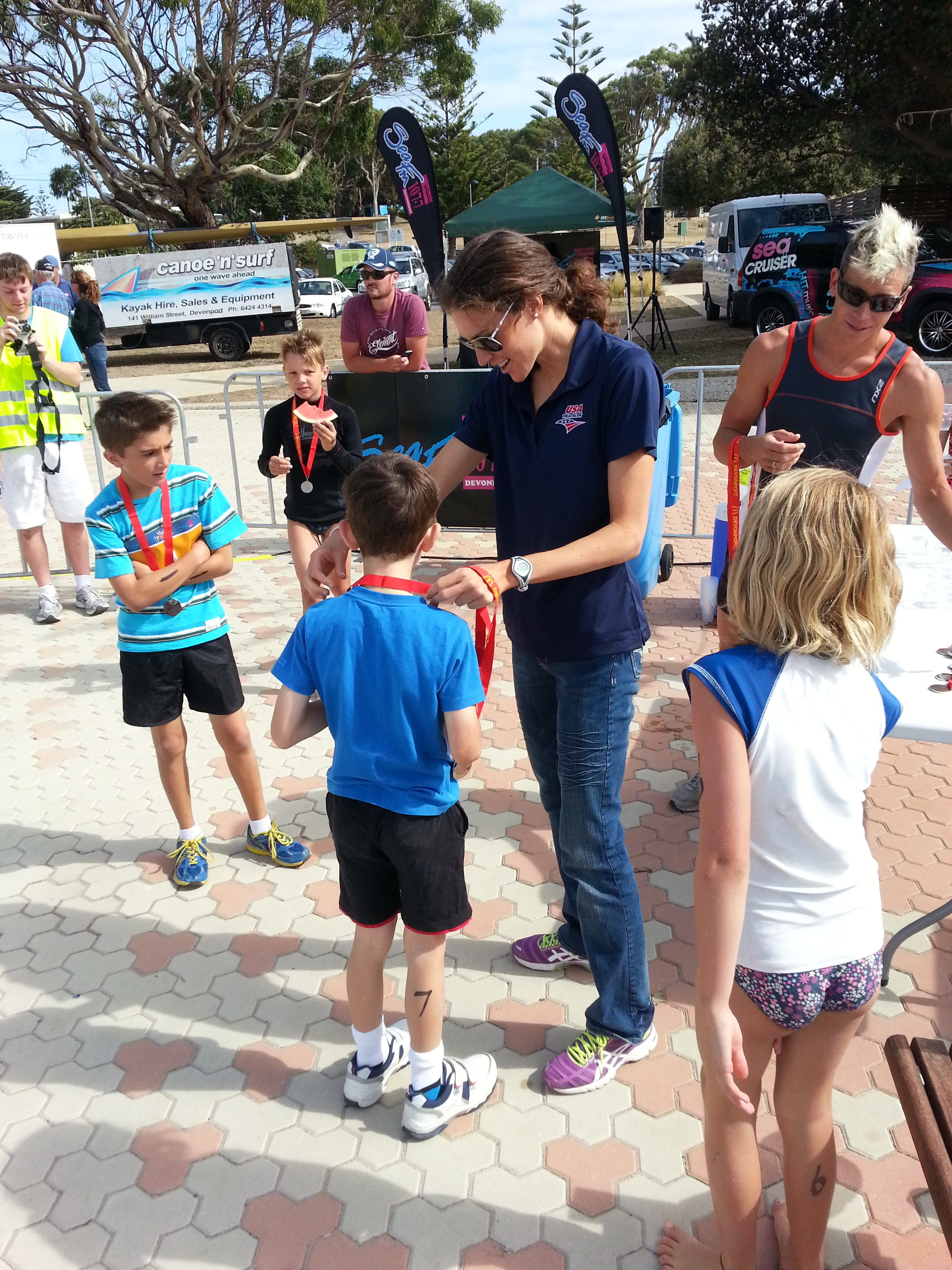 Gwen handing out medals at a triathlon