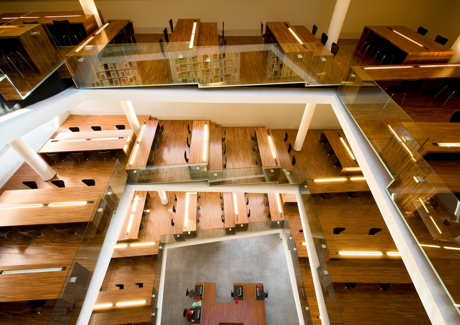 view of reading tables from upper level     These ramps are the reading rooms. They are levelled with mahogany platforms on which the reading tables are set. These are also made of mahogany block-wood and house the up-lights for ambient lighting.