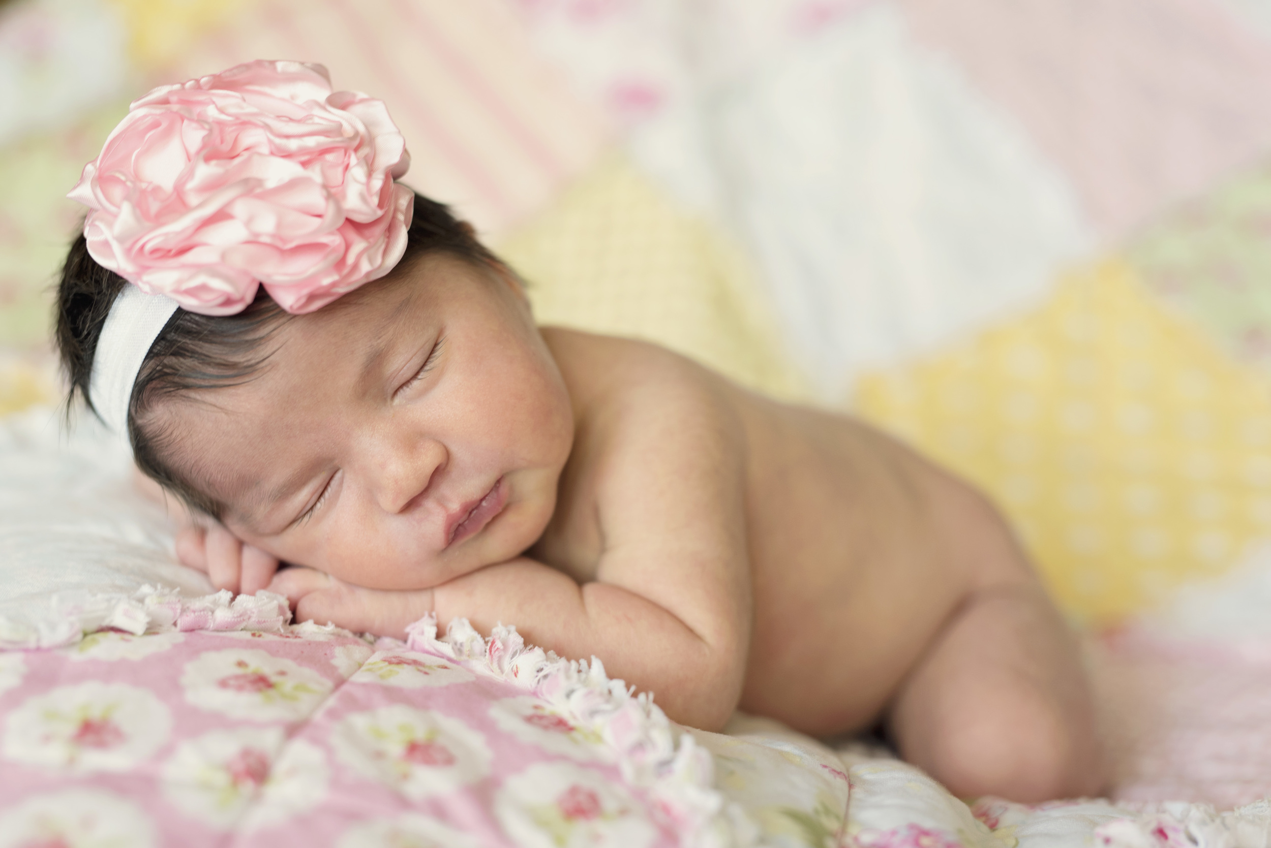 newborn girl with quilt and pink bow