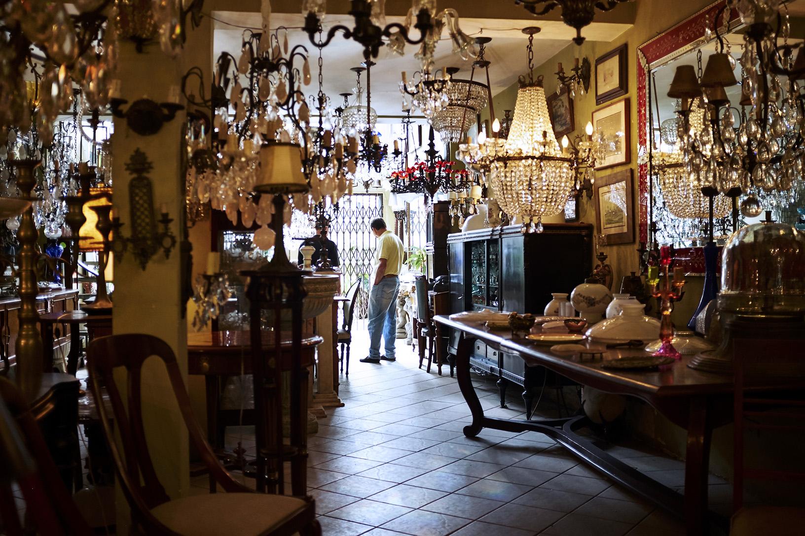 Jair recebendo um cliente em sua loja que hora lembra o palácio de um doge, hora um pequeno palacete dos Habsburgo.