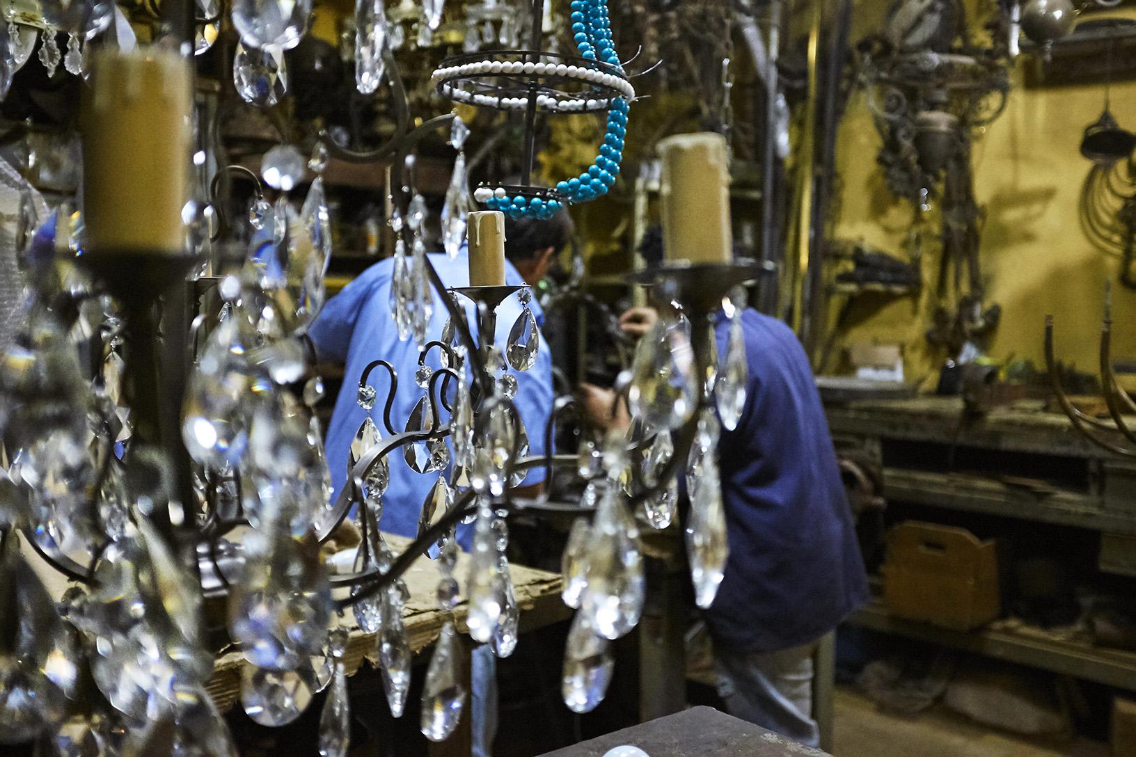 Um lustre de cristal espera ser atendido na oficina