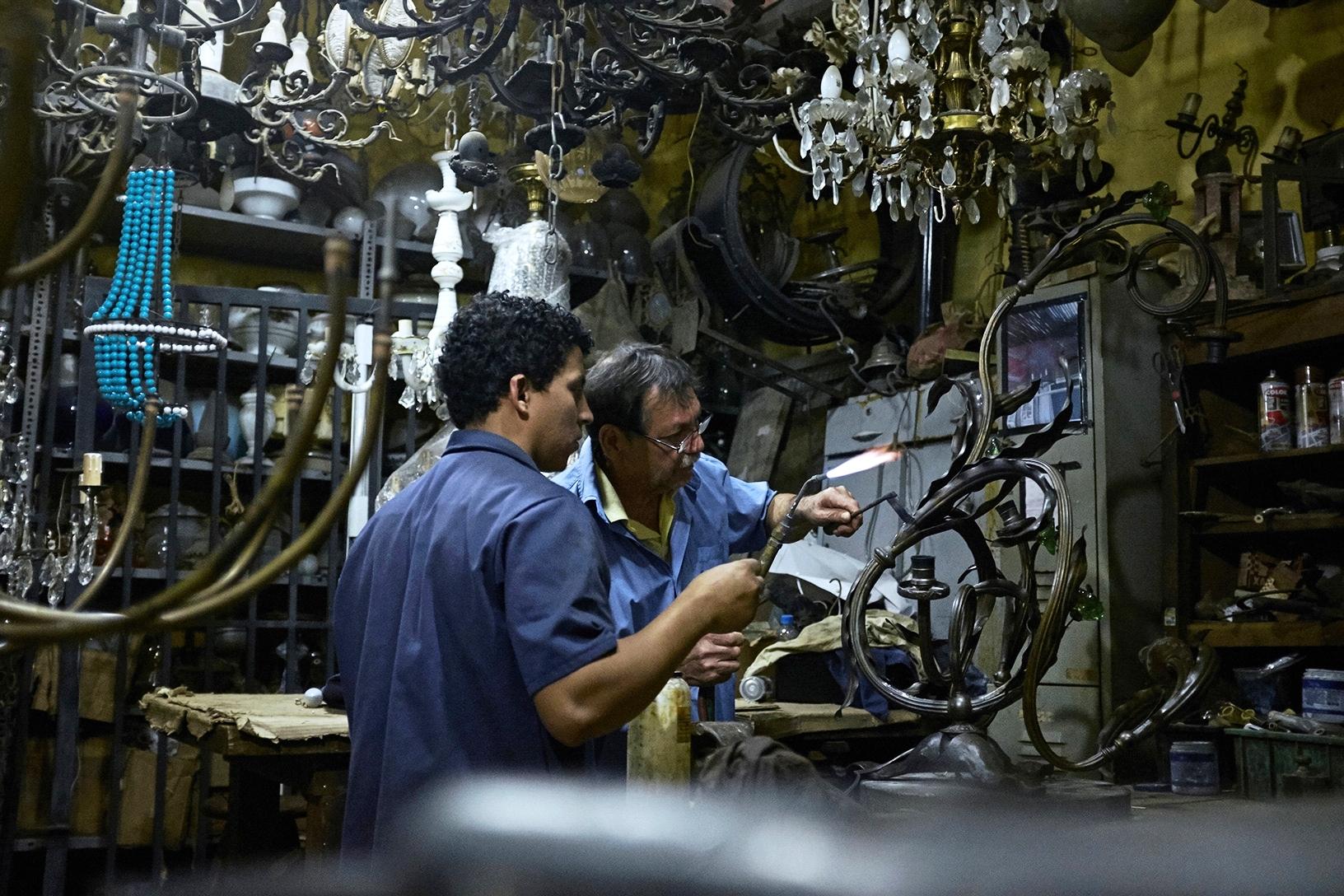 Jair e Adriano restaurando uma arandela francesa art nouveau.