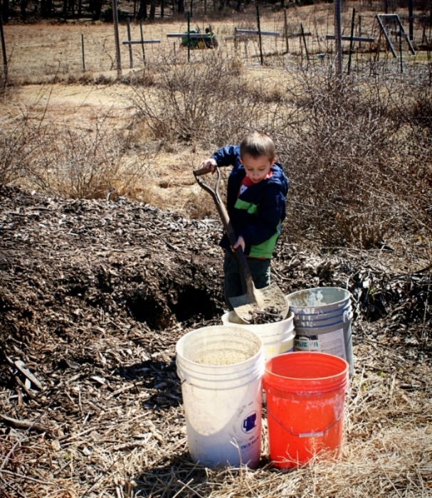 Our youngest gardener shoveling mulch into buckets destined for the bed.