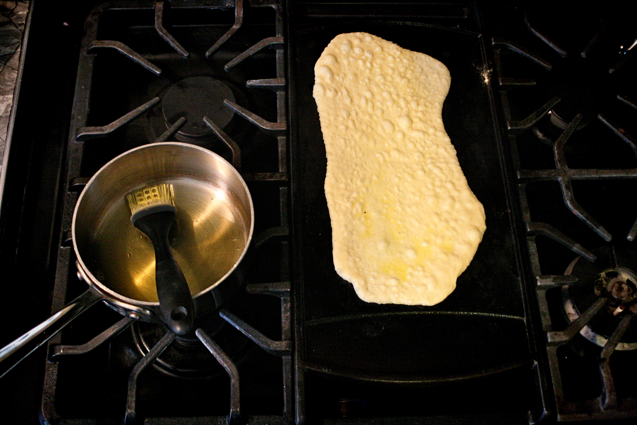 I have never used our grill to cook the naan. While I bet it would be smoky and delicious (and leave me with a cleaner kitchen!), I have never figured out where or how I would roll out the dough outside. So, I stick with the cast iron slab that fits over the long center burner of our stove. I imagine a cast iron pan would work just as well; you would simply need to make sure you made the dough balls an appropriate size and shape to fit your pan.