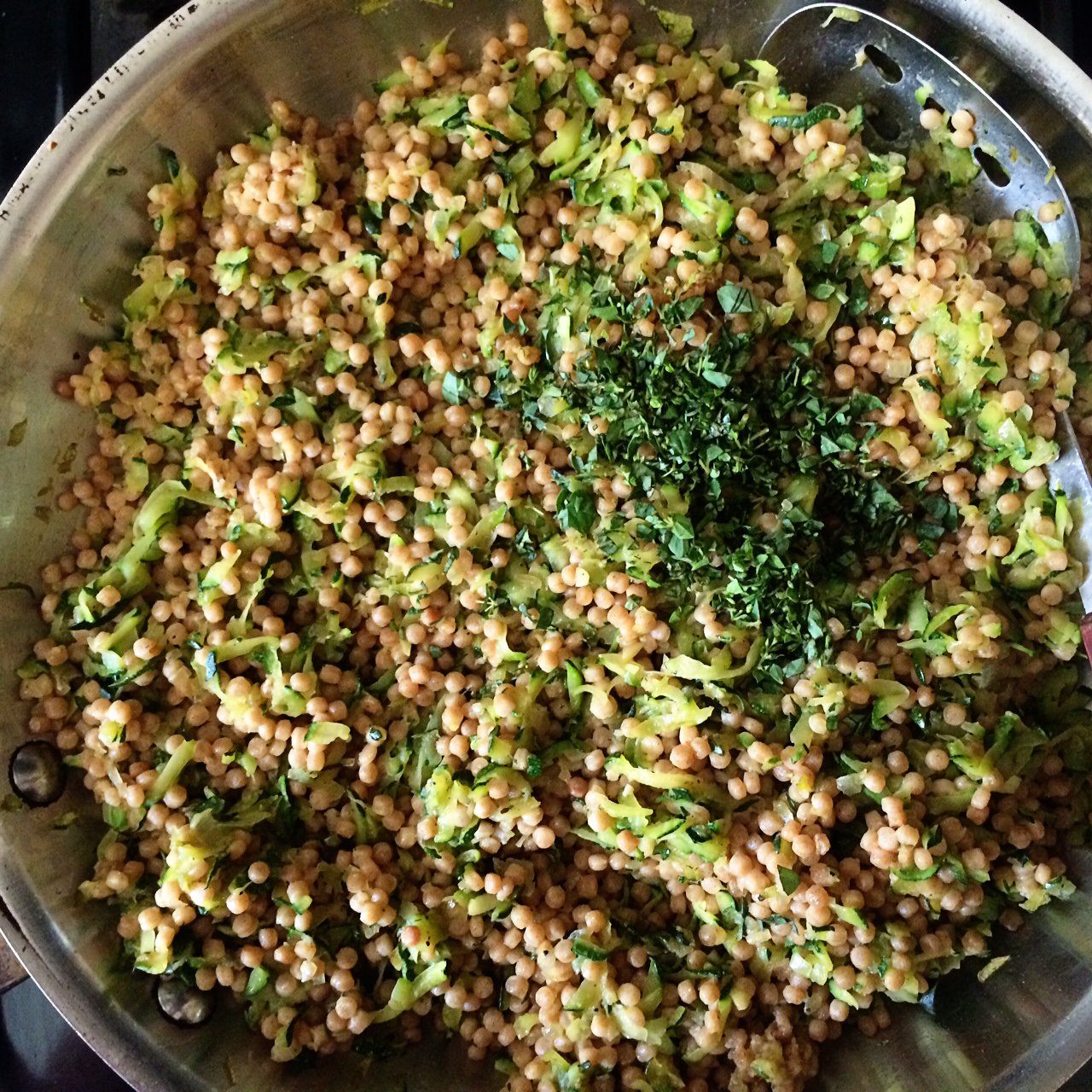 Happily, once the couscous was stirred into the zucchini, it broke right up and each little nubbin became  coated with the juices and oil present from the sautéed veggies. It was almost perfect, but  needed a little something more, so I ran to the garden to cut some oregano to toss in.